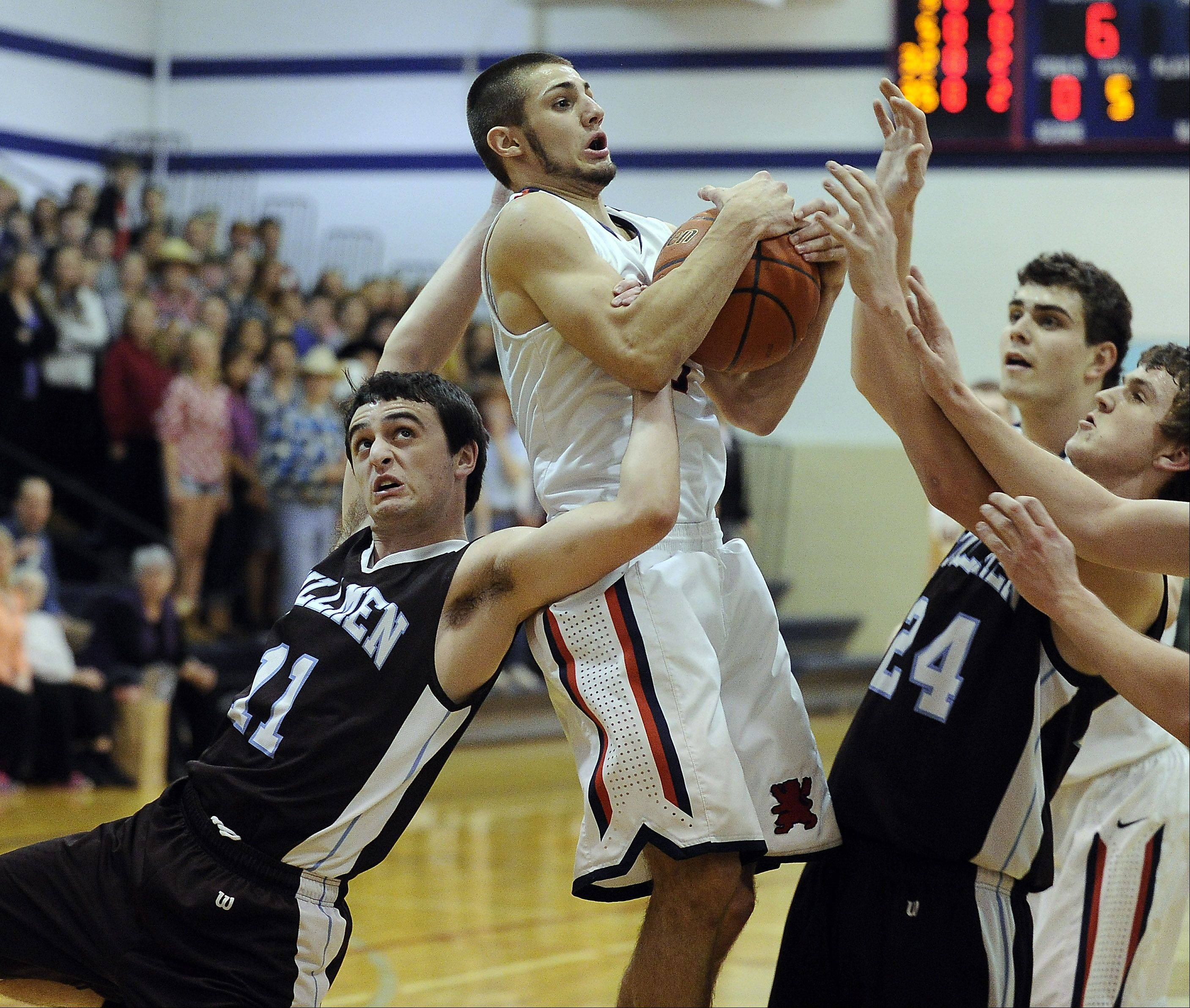 St. Viator's DJ Morris battles with Joliet Catholic Academy's Grant Larussa for the ball during Thursday's game at St. Viator.