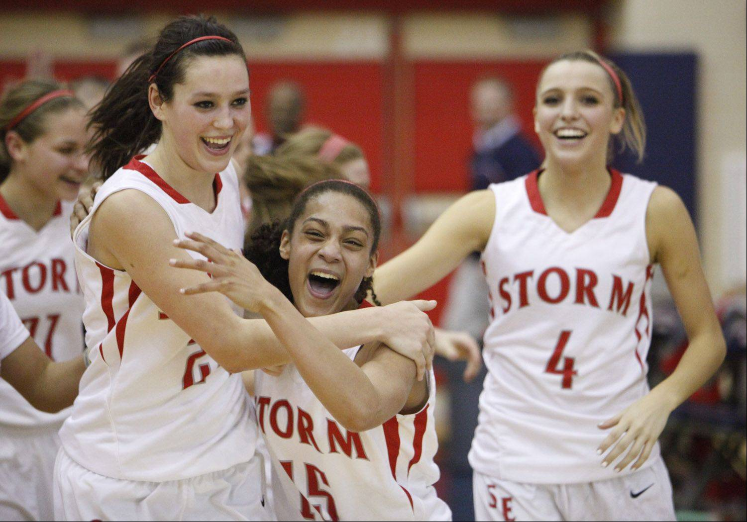 South Elgin teammates Kennede Miller, left, Becca Smith and Savanah Uveges celebrate their team's regional win Friday night in South Elgin.