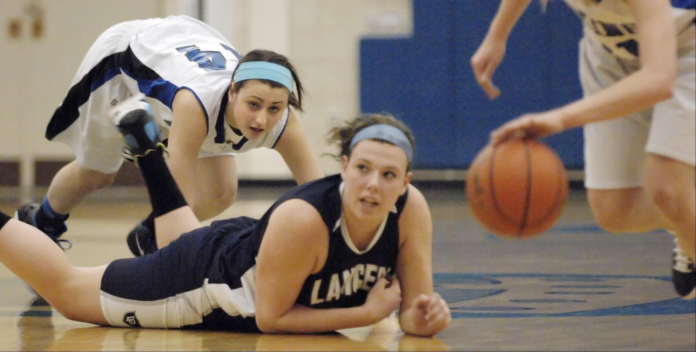 Geneva's Abby Novak and Lake Park's Alexis Hahn watch from the floor as the Viking's Michaela Loebel recovers the loose ball Tuesday in Geneva.