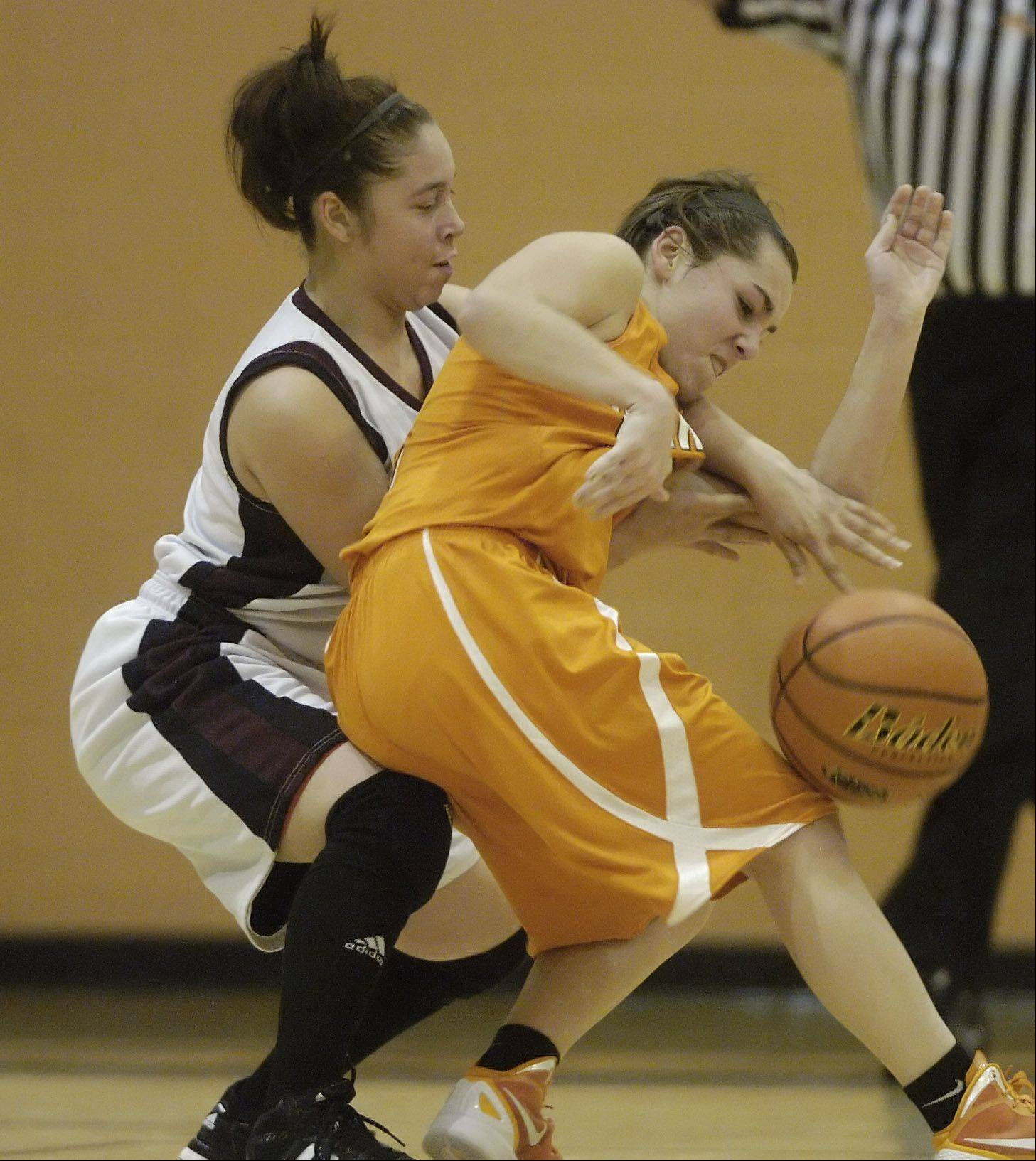 Hersey's Jen Hall, right, draws contact from Zion-Benton's Carlie Fernandez during Wednesday's regional semifinal at Hersey High School in Arlington Heights.