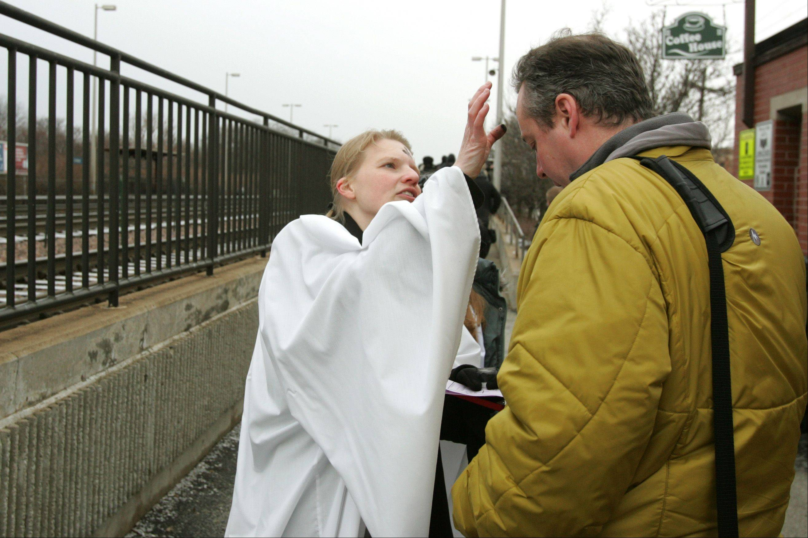 The Rev. Emily Mellott, pastor of Calvary Episcopal Church in Lombard, dispenses Ashes to Go to commuter Don Feeley on Wednesday morning at the Lombard train station.