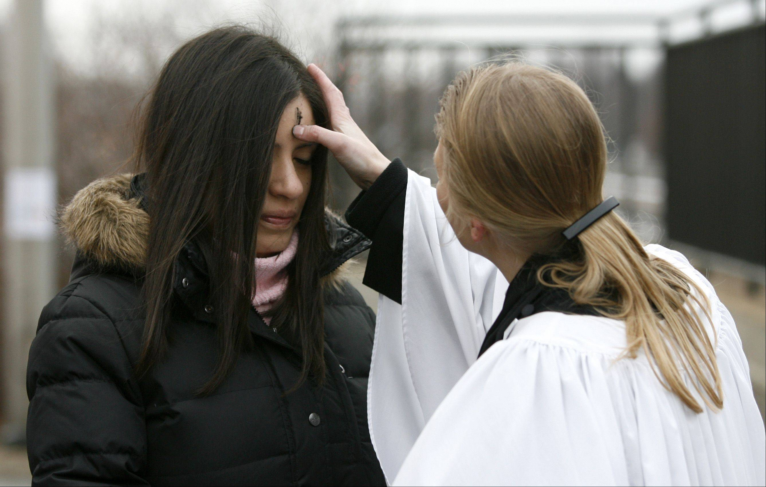 Maritza Summers receives ashes Wednesday morning from the Rev. Emily Mellott, pastor of Calvary Episcopal Church in Lombard, during the third annual offering of Ashes to Go at the Lombard train station.