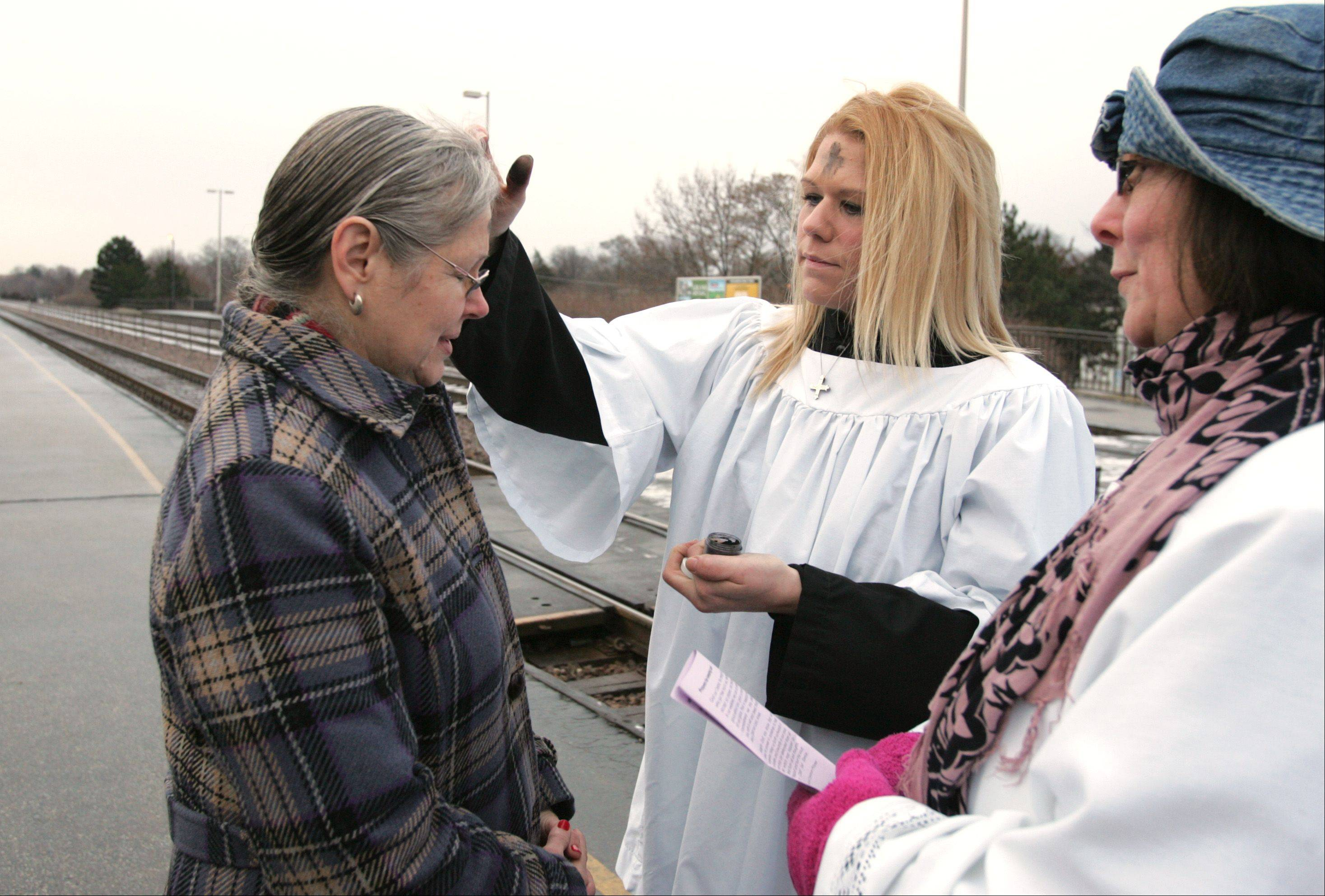 Maureen Elliot of Calvary Episcopal Church in Lombard dispenses Ashes to Go to commuter Marilyn Stein at the Lombard train station Wednesday morning as Ruth Ann Pfohl offers a prayer. A team from the church gave ashes to 107 people Wednesday morning.