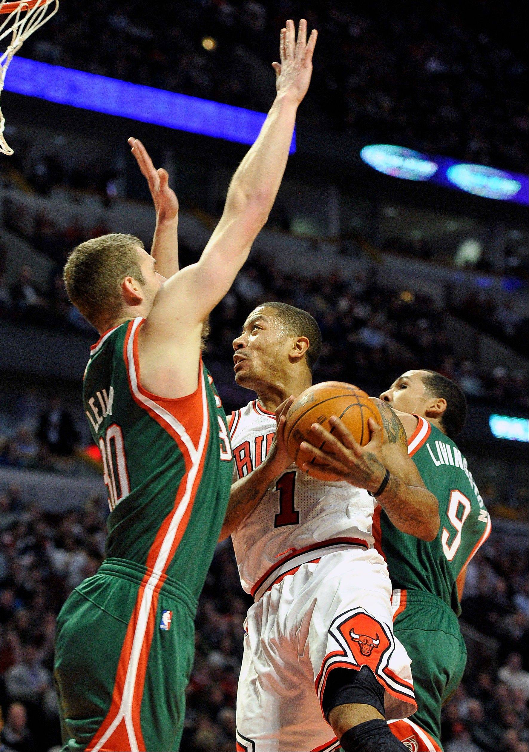 Milwaukee Bucks' Jon Leuer, left, defends as Bulls guard Derrick Rose drives to the basket Wednesday during the second half. The Bulls defeated the Bucks 110-91.