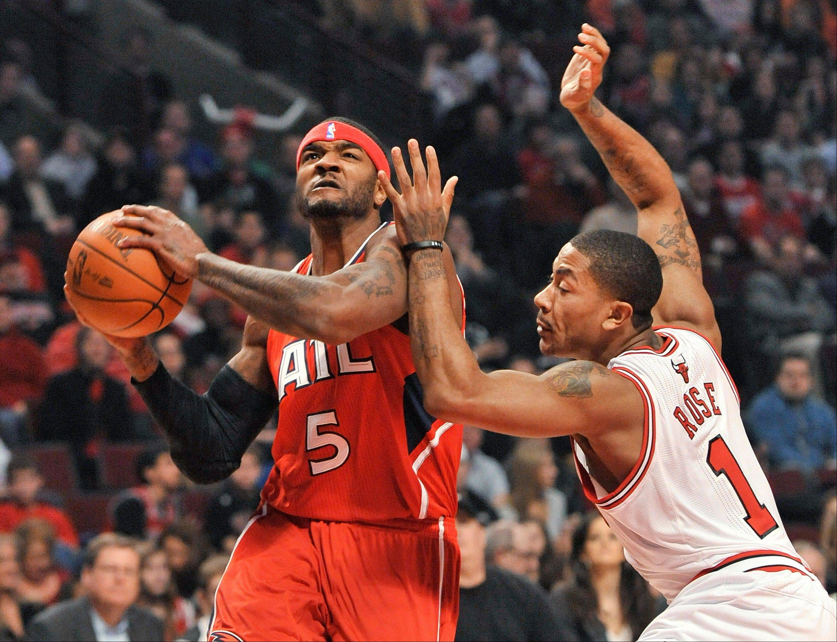 Derrick Rose, here defending Atlanta forward Josh Smith, says his back is feeling fine after his return to the floor Monday against the Hawks.