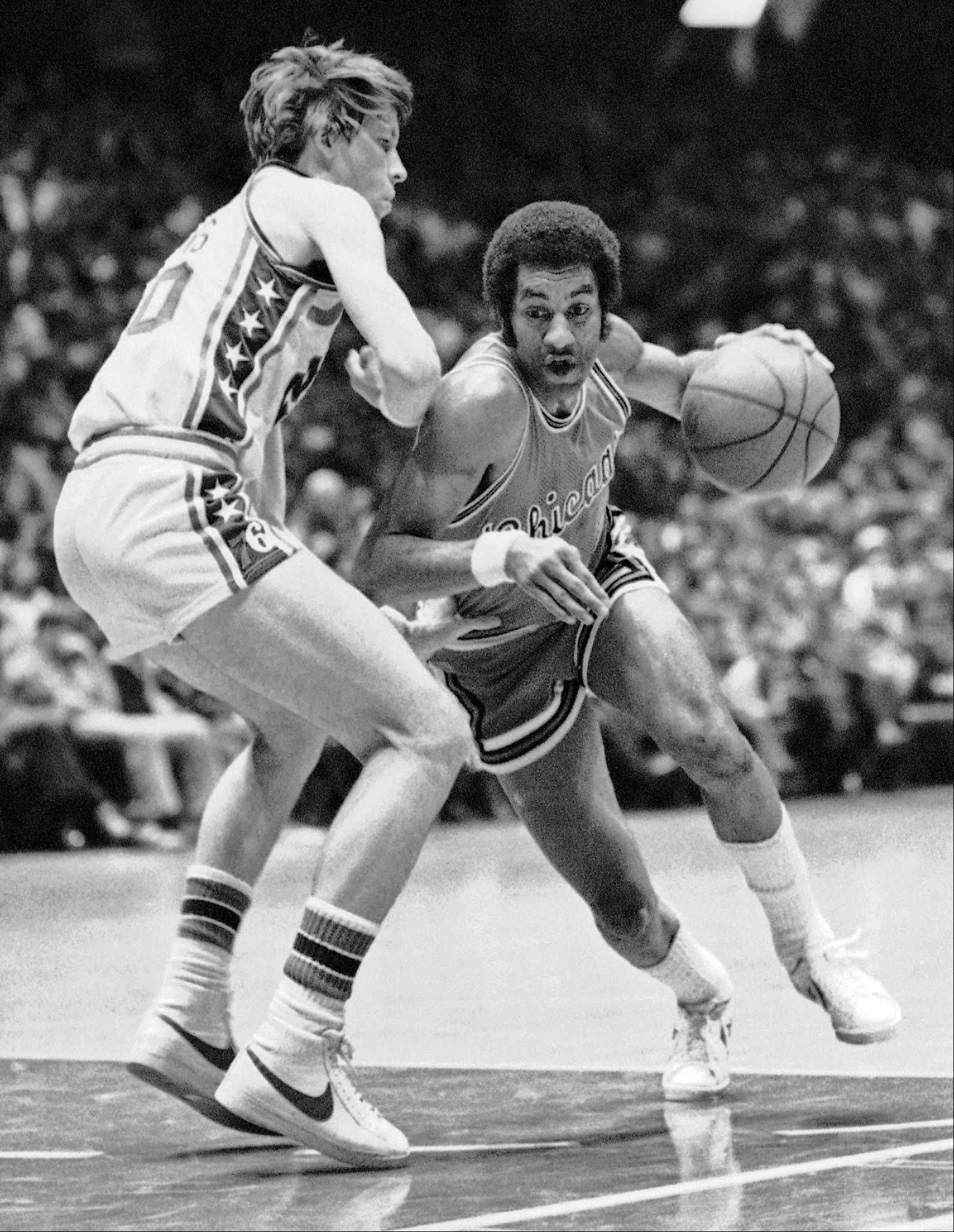 In this March 17, 1976 file photo, Philadelphia 76ers' Doug Collins, left, defends as Chicago Bulls guard Norm Van Lier dribbles past him during the first half of an NBA basketball game in Philadelphia.