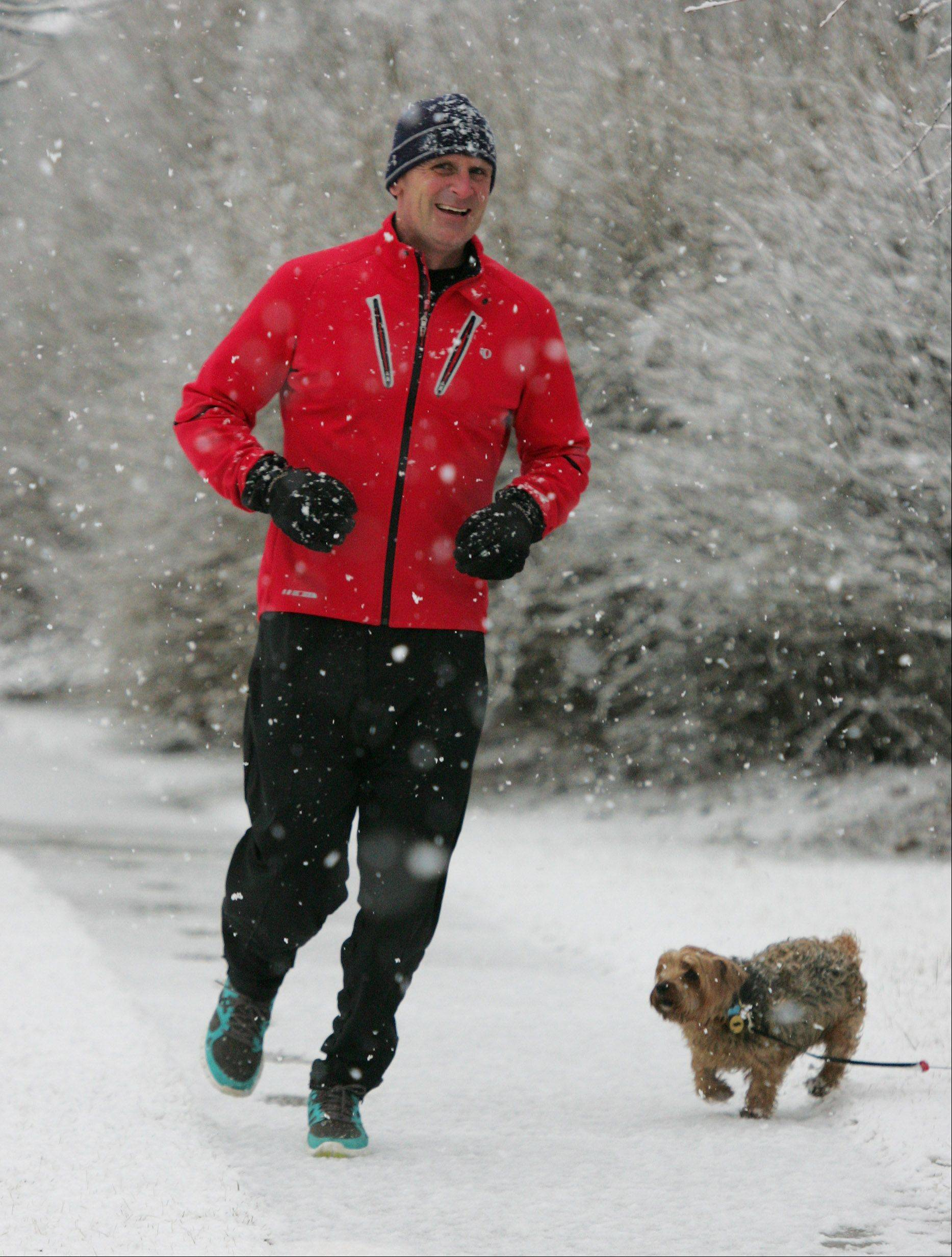Rob Rayl of Mundelein runs by a dog as he jogs in the snow along Huntington Drive Thursday in Lake County. The snow was expected to disrupt afternoon commuter traffic.