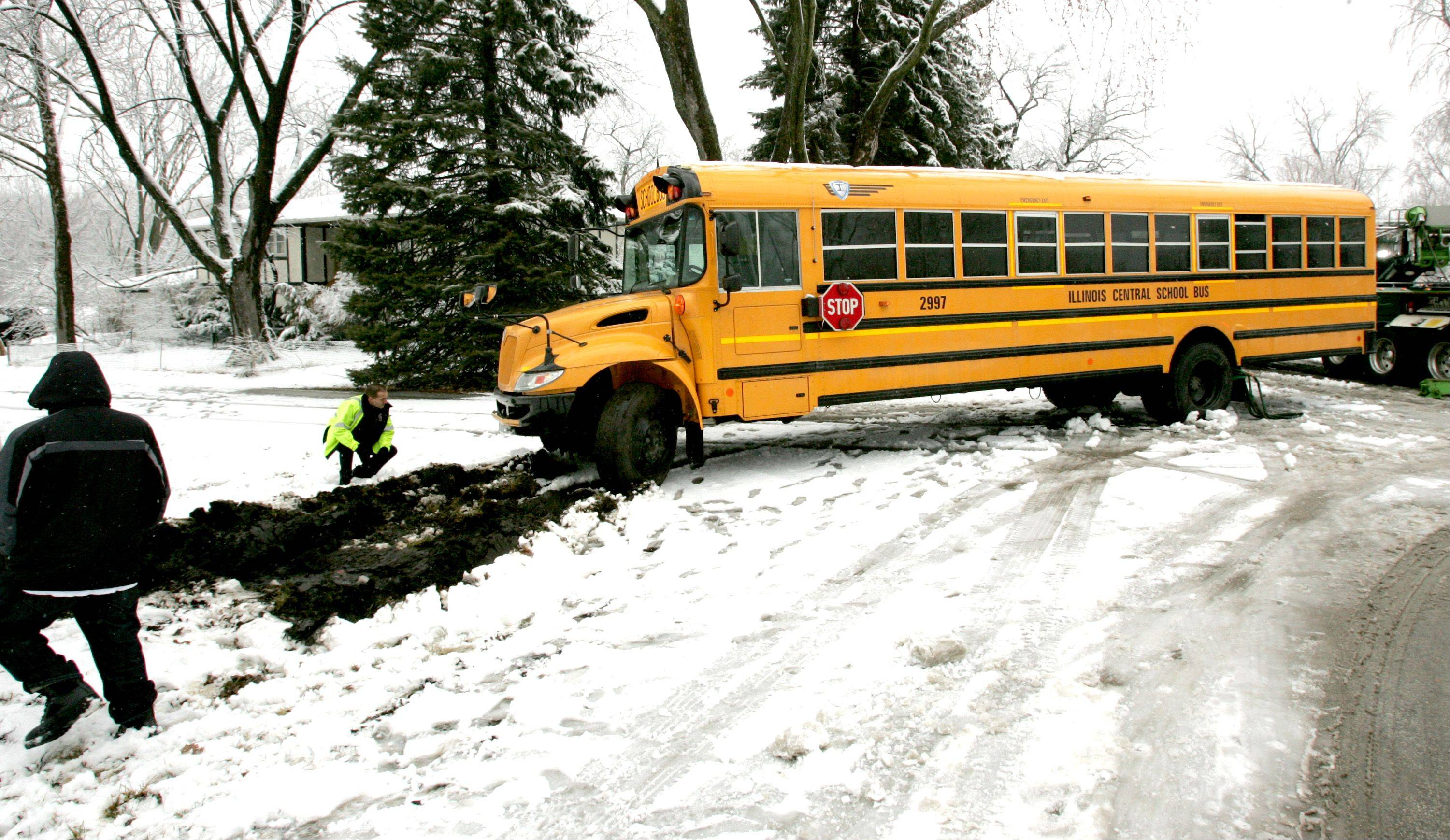 A tow truck pulls a school bus back on the road Friday after it slid off an icy Lisle street and into a resident's yard. None of the roughly two dozen students aboard were injured.