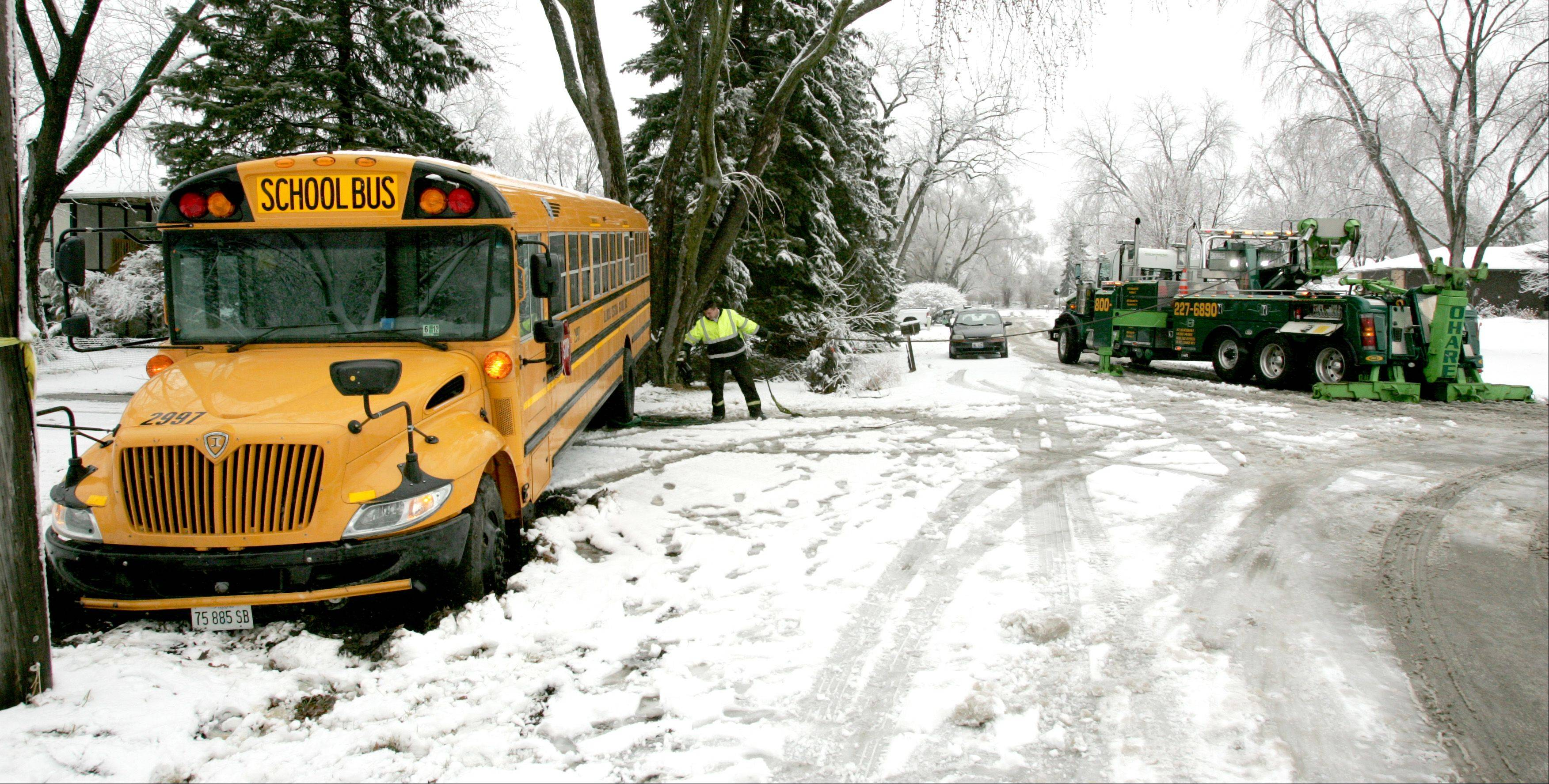 O'Hare Towing Service driver Matt Bartlett prepares to pull a school bus that slid off a Lisle street Friday and became stuck in the snow and mud. None of the two dozen students on board were injured.
