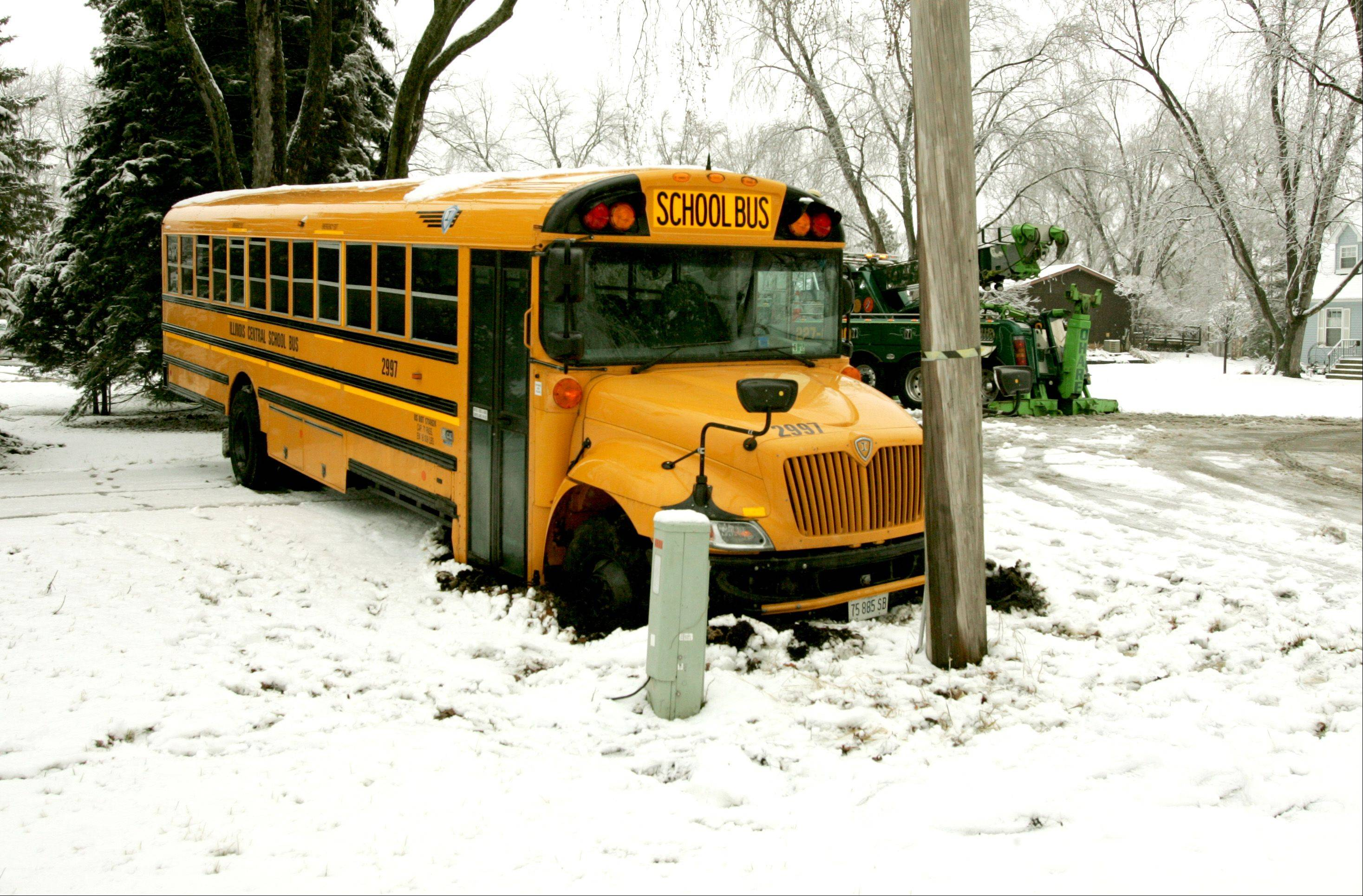 An Illinois Central school bus carrying about two dozen Lisle students skidded off an icy street Friday and wound up stuck in the snow and mud of a resident's yard. No injuries were reported.