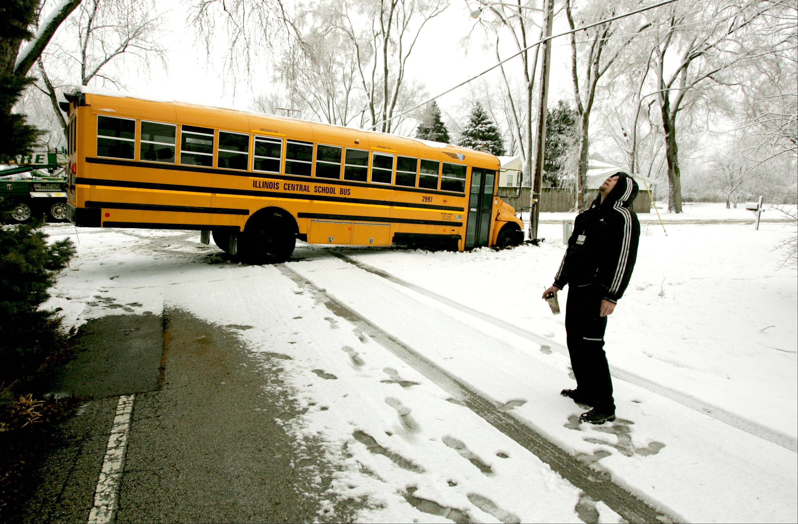 "A school bus skidded on ice at the corner of Lacey and Dumoulin in Lisle. Raymond Rowe, above, waits for the bus's removal, as he is temporarily 'boxed in"" in his own driveway."