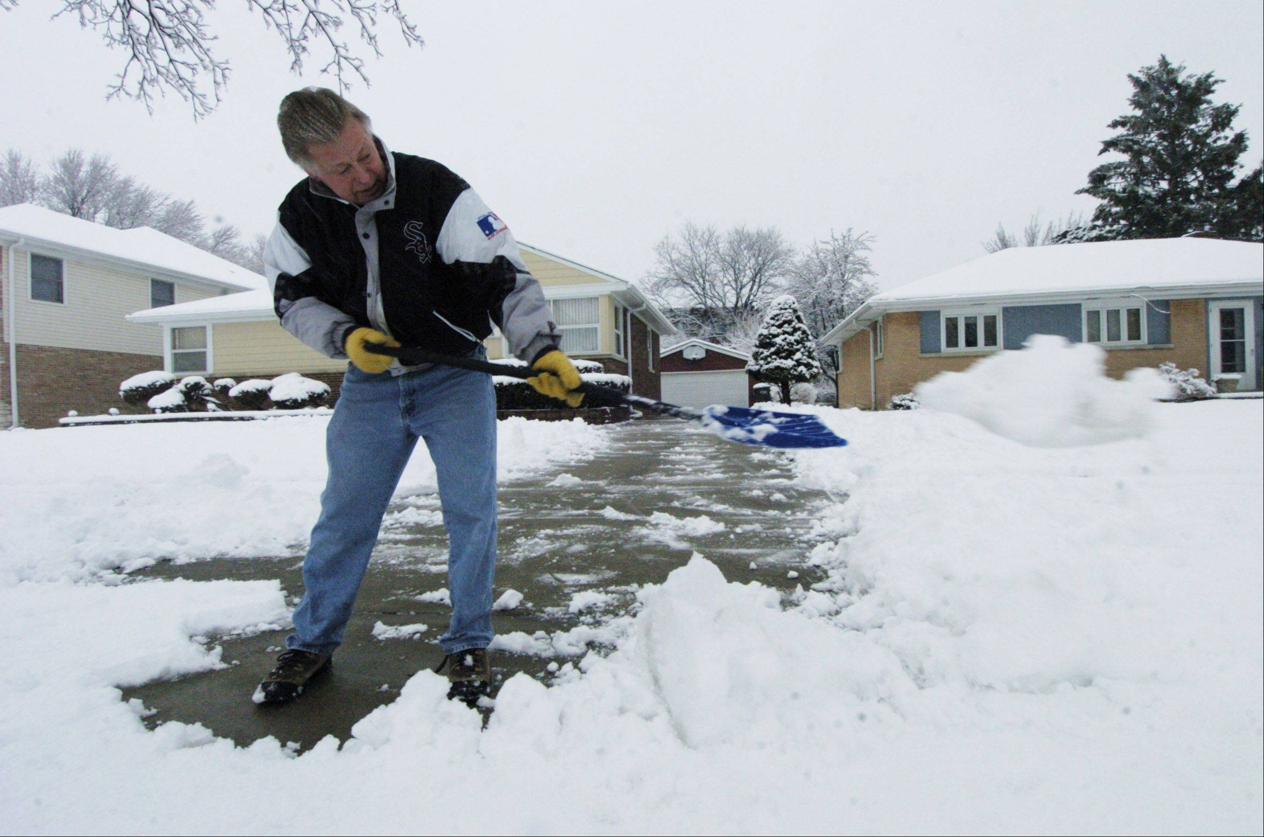Don Sosnowski shovels wet, heavy snow in front of his home on Busse Ave. in Mount Prospect Friday morning.