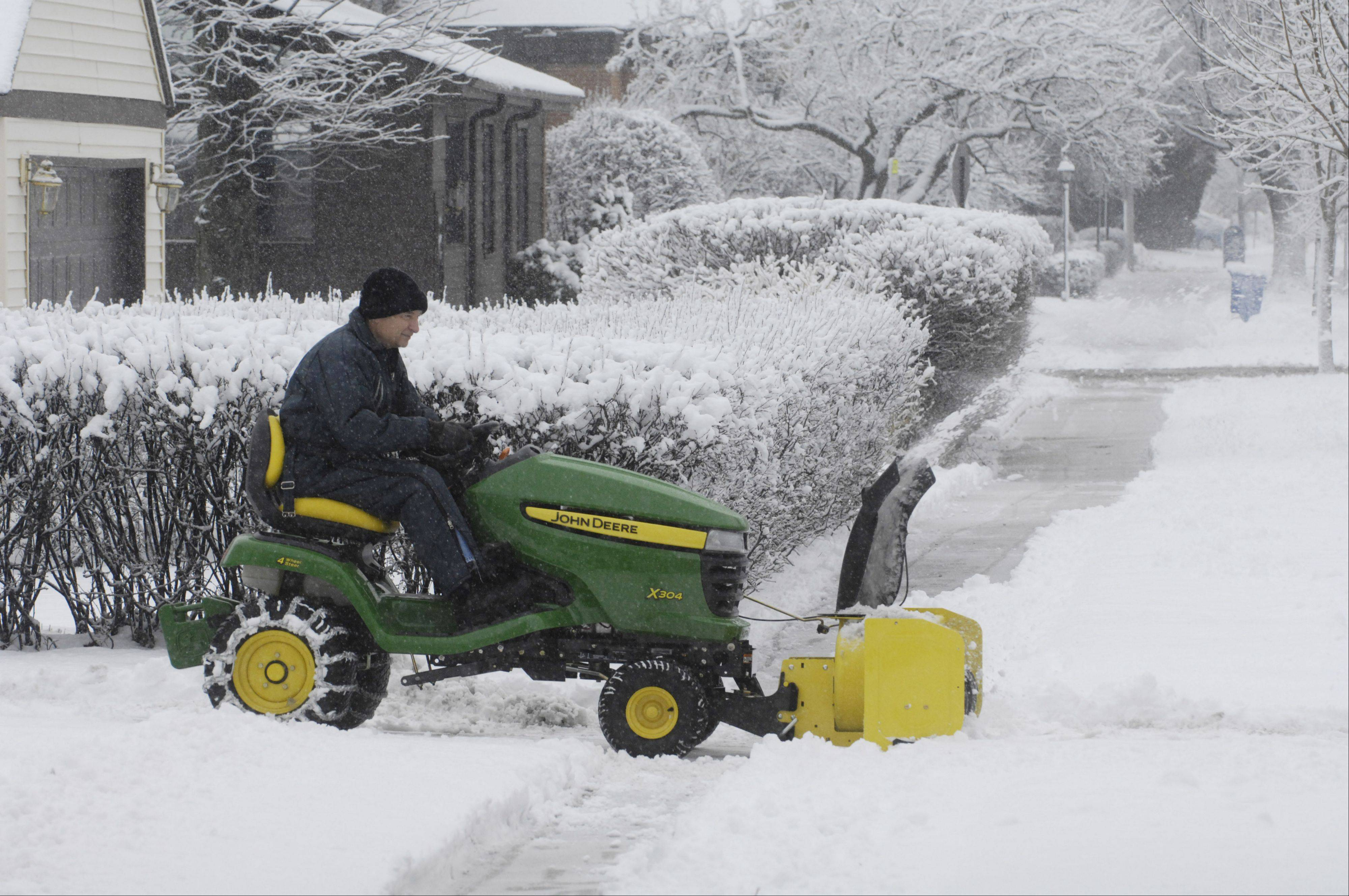 Leo Wajda uses a tractor to plow his driveway in Mount Prospect Friday morning.