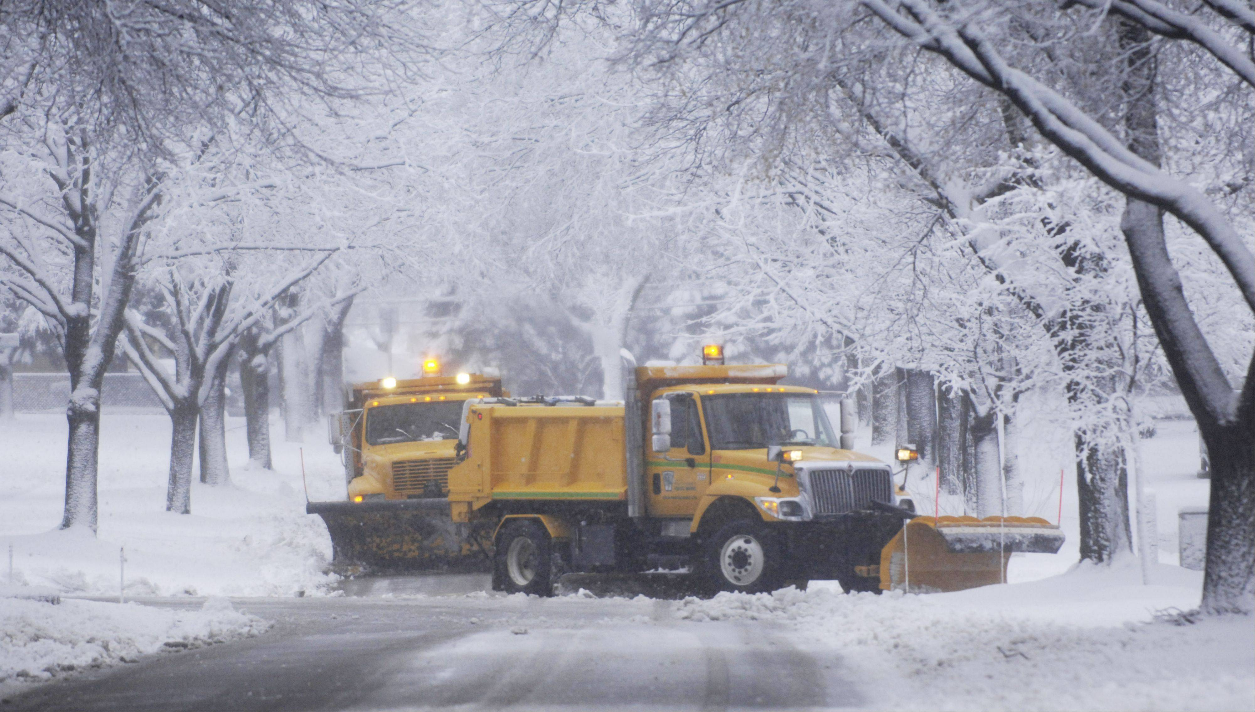 Public works plows clear snow from neighborhood streets in Mount Prospect Friday morning.