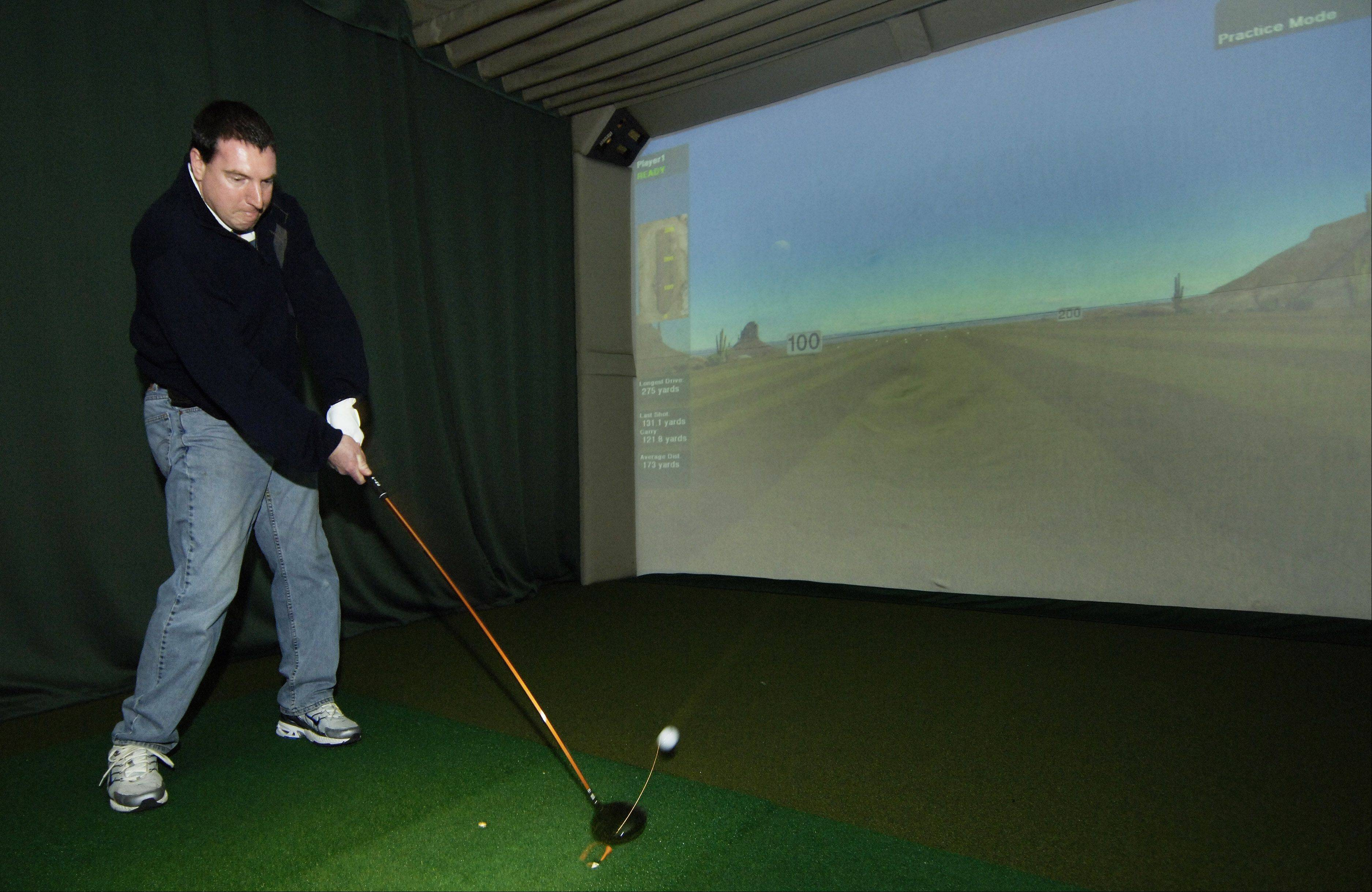Noel Hughes of Chicago takes a swing while using the simulator of the Vulcan Golf Lab, Geneva, at the Chicago Golf Show at the Rosemont Convention Center.