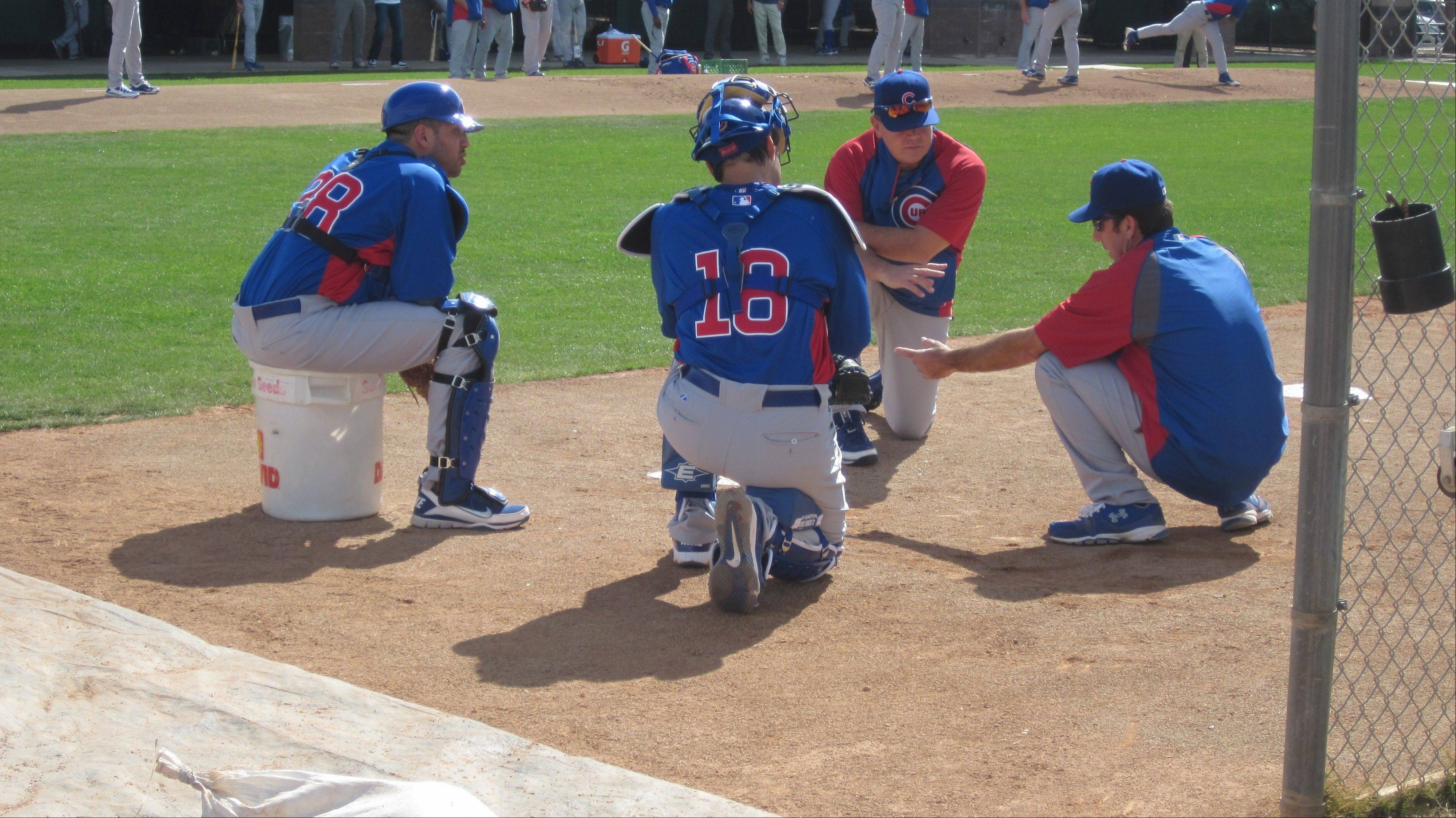 After going through several catching drills, Cubs players and coaches talk about what they accomplished and what's needed. From left to right are Jason Jaramillo (38), Geovany Soto (18), instructor Marty Pevey and coach Mike Borzello.