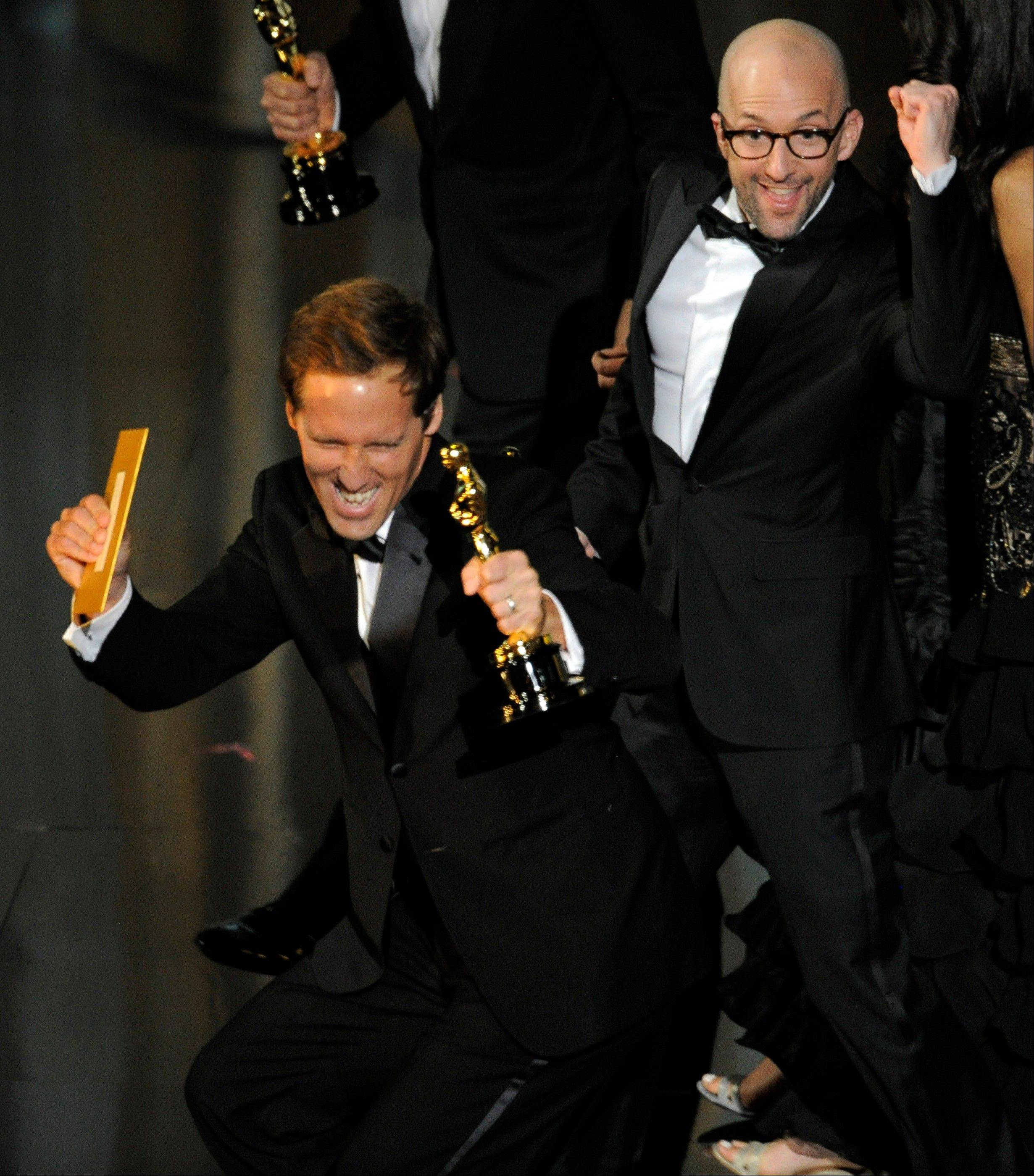 "Nat Faxon, left, and Jim Rash accept the Oscar for Best Adapted Screenplay for ""The Descendants."""