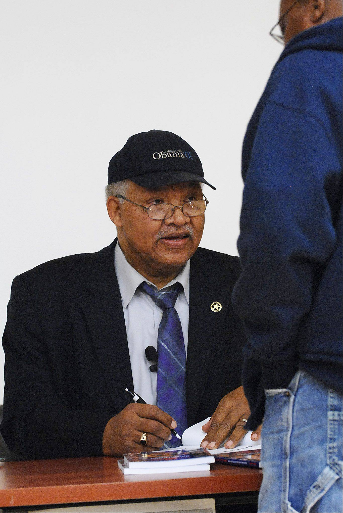 Robert Moore is one of only 68 African Americans appointed to serve as a United States marshals since the position was created in 1789. He wrote a book about the contributions of black marshals after realizing they were overlooked in history texts. Moore signs a copy of his book after a speech Sunday at the Gail Borden Public Library in Elgin.