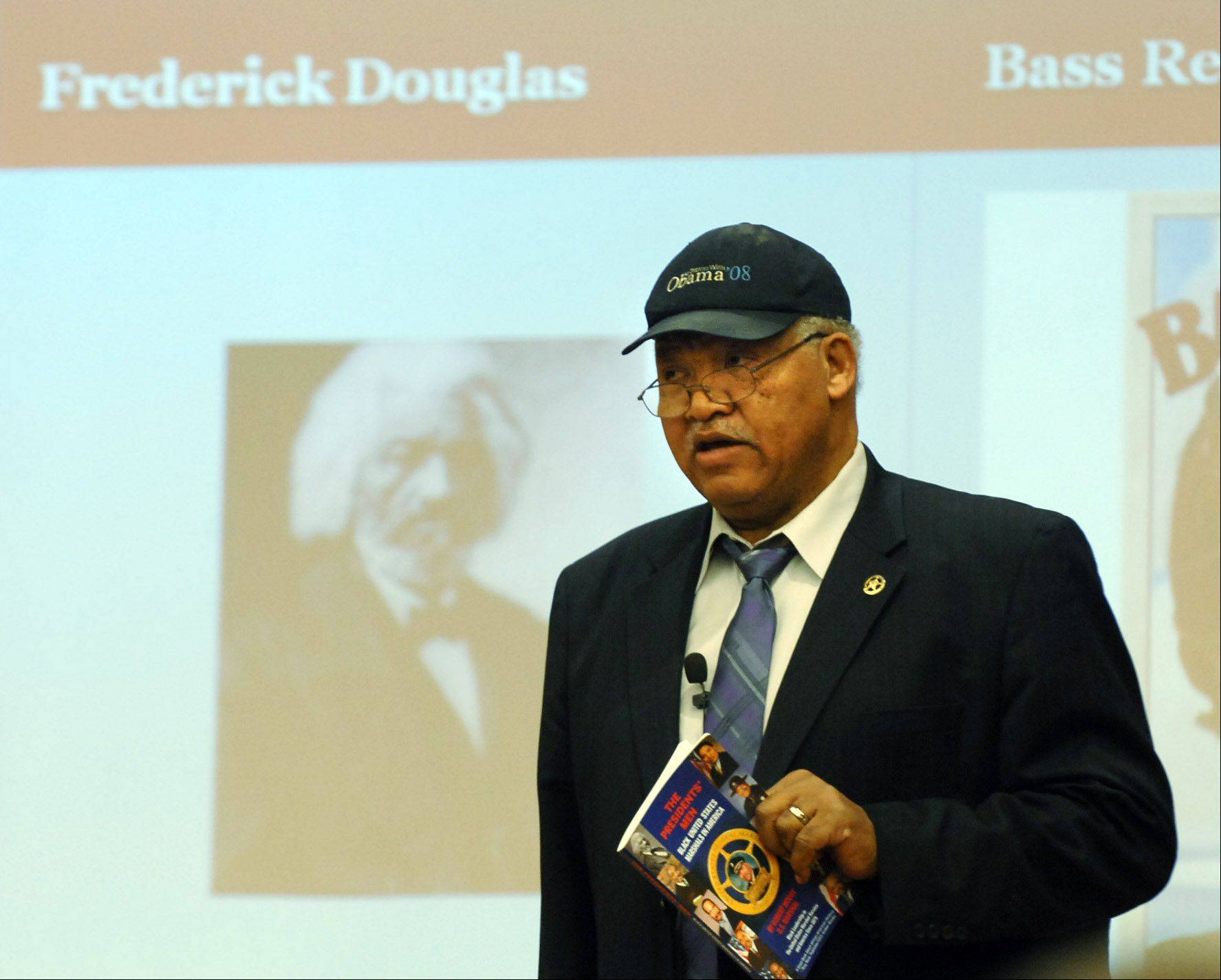 Robert Moore is one of only 68 African Americans appointed to be United States marshals since the position was created in 1789. He wrote a book about the contributions of black marshals after realizing they were overlooked in history texts. Moore holds a copy of his book during a speech Sunday at the Gail Borden Public Library in Elgin.
