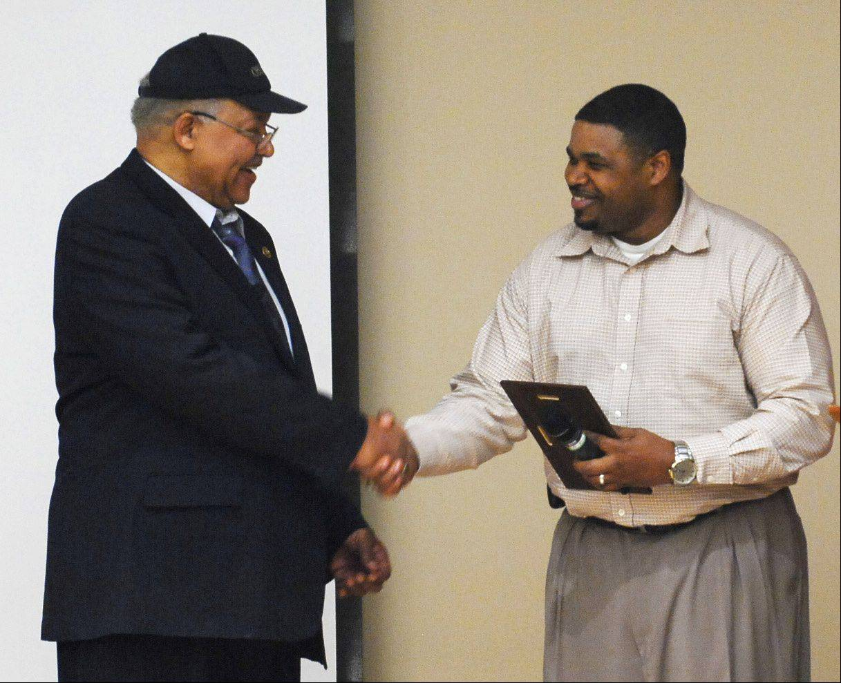 Sgt. Gary Neal of the Elgin Police Department presents a plaque to Robert Moore, who wrote a book about the contributions of black U.S. marshals after realizing they were overlooked in history texts. Moore, who was appointed to be a marshal by President Bill Clinton, discussed his book Sunday at the Gail Borden Public Library in Elgin.