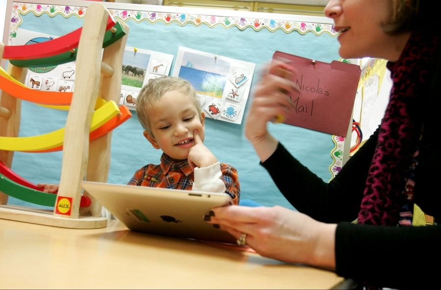 Three-year-old Reco Capparelli uses an iPad during speech therapy with speech pathologist Nicole MacKinnon at Jefferson Preschool in Wheaton-Warrenville Unit District 200.