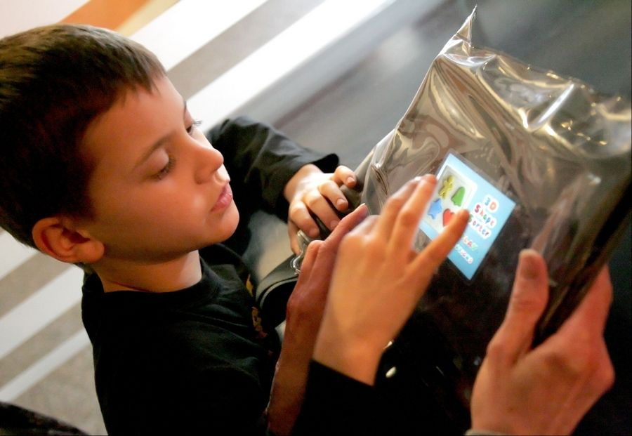 Justin Hafner, 9, of Joliet, works with an iPad at Giant Steps school in Lisle. Educators rave about the learning that students with autism can accomplish on the iPad.