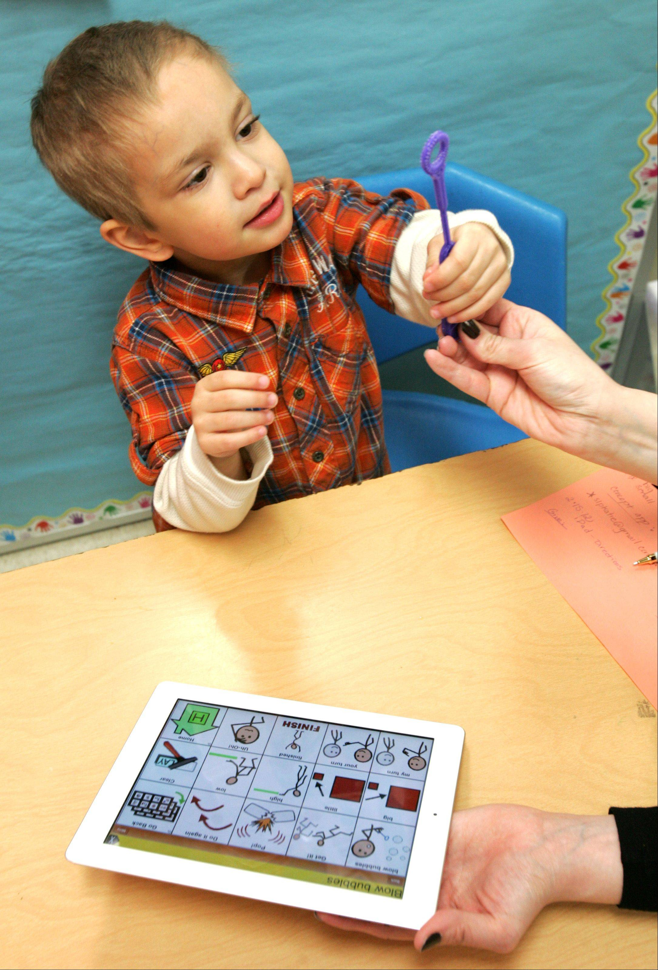 Reco Capparelli, 3, uses an iPad to blow bubbles -- part of an exercise on following directions during a therapy session with Wheaton-Warrenville Unit District 200 speech pathologist Nicole MacKinnon.