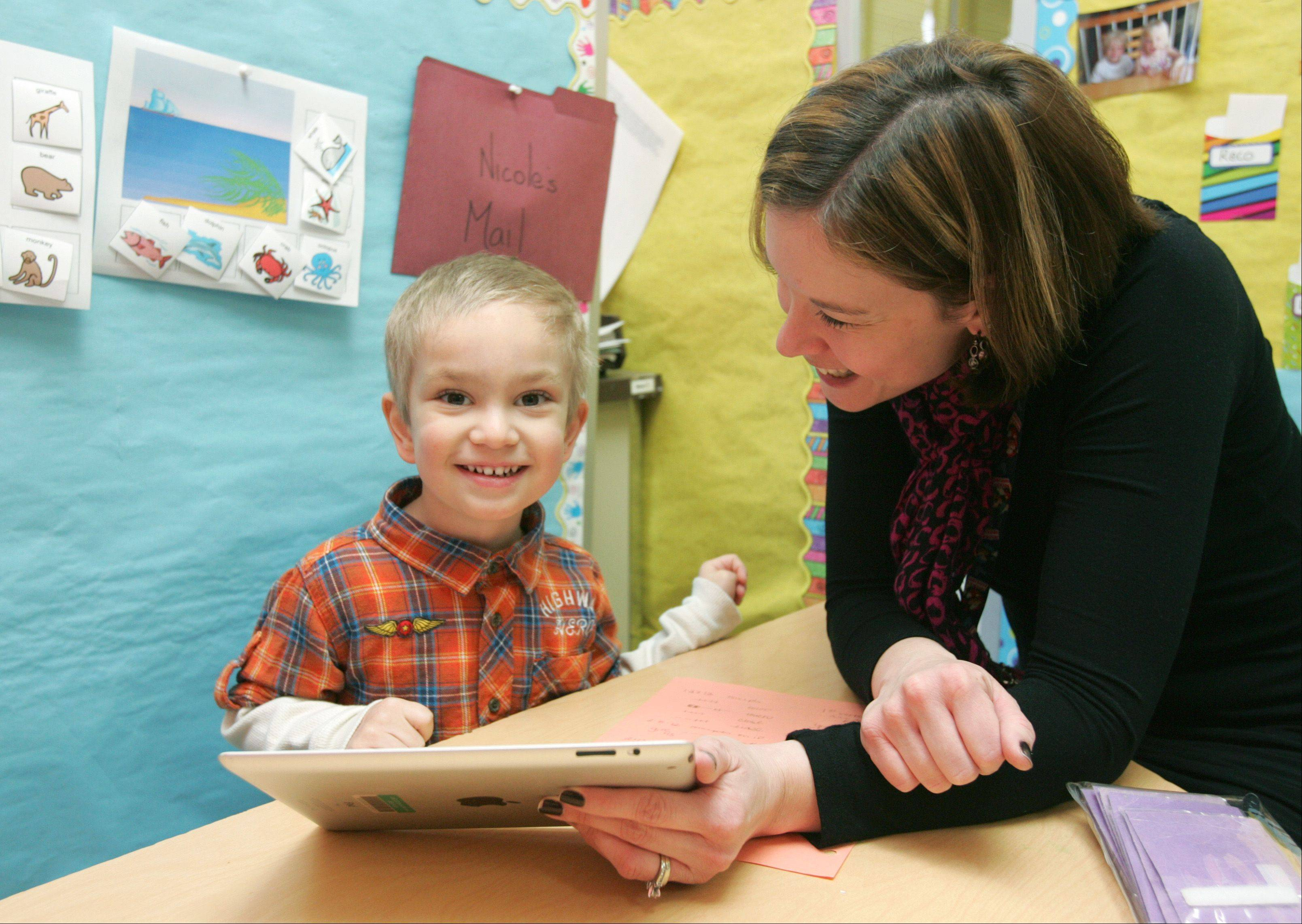 "Three-year-old Reco Capparelli of Wheaton uses an iPad during therapy with speech pathologist Nicole MacKinnon at Jefferson Preschool in Wheaton-Warrenville Unit District 200. ""I think his speech has definitely improved. He's more spontaneous; he talks more,"" his mother, Gemma, said about Reco's progress since starting to use an iPad in January."