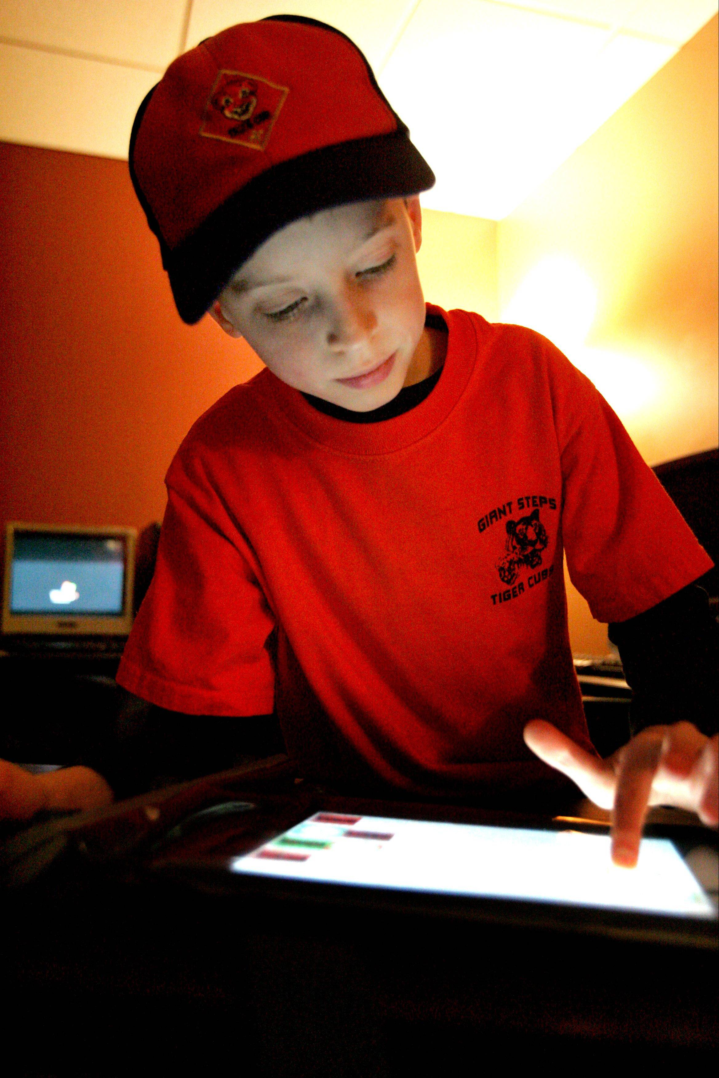 Joshua Brooks, 7 uses an iPad at Giant Steps school in Lisle. His mother, Lisa, said an iPad Joshua uses at home helps him complete tasks and learn how to behave in social situations.