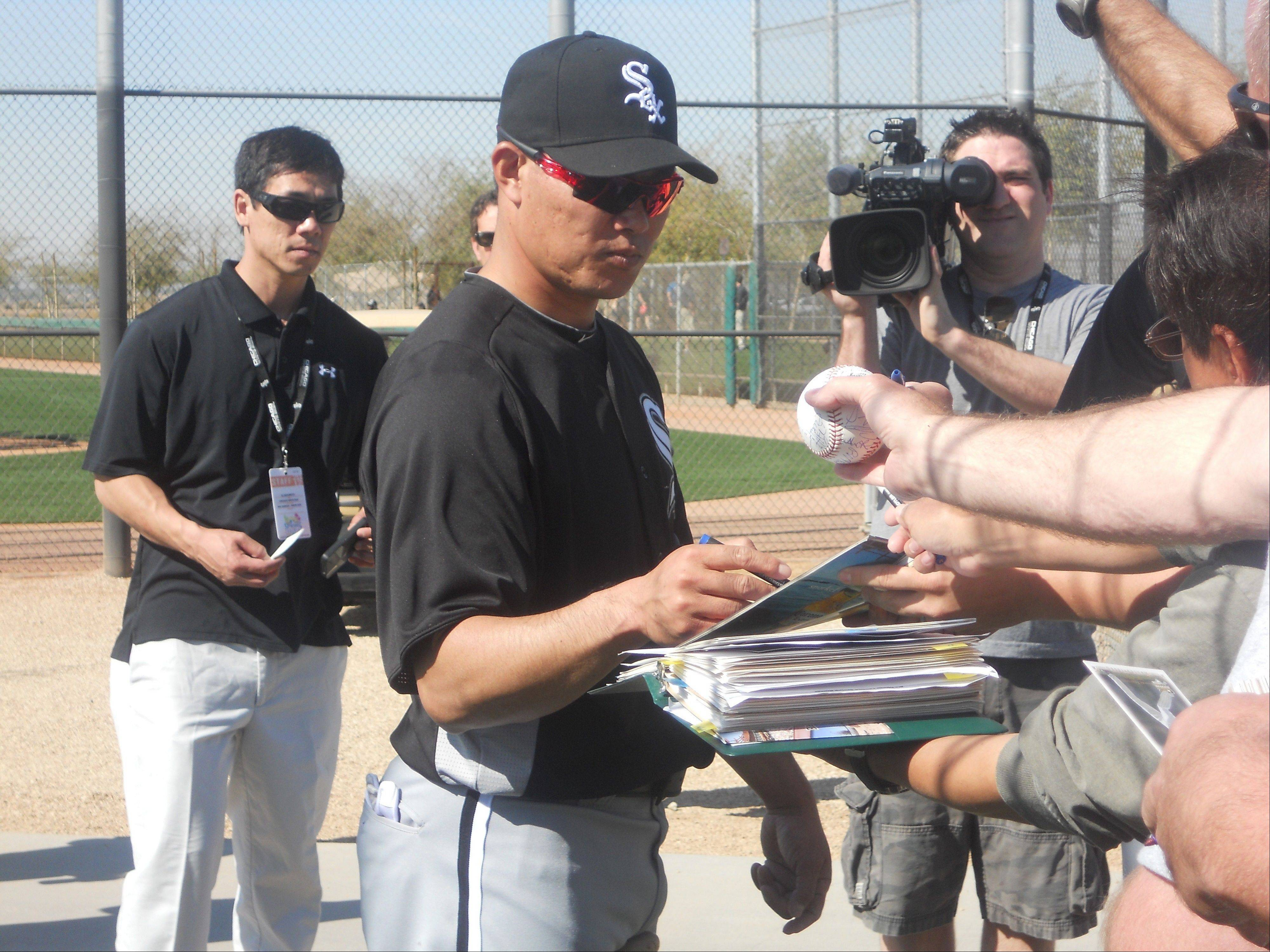 Kosuke Fukudome signs an autograph for a fan Sunday at White Sox camp in Glendale, Ariz. Fukudome gives the Sox a low-risk option in the outfield and is likely just a stopgap as the South Siders wait for one of three prospects to develop.