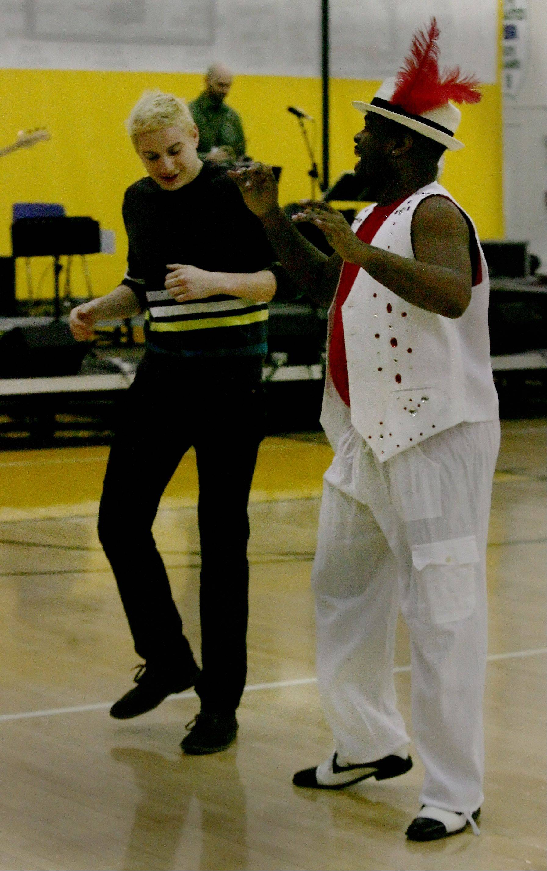 Senior Daniel Shtivelberg, left, performs with Pierre Cameron who dances with Orquestra de Samba during the Odyssey Fine Arts Festival at Stevenson High School in Lincolnshire. The two-day event brings in writers, performers and artists to broaden the exposure of the arts for students.