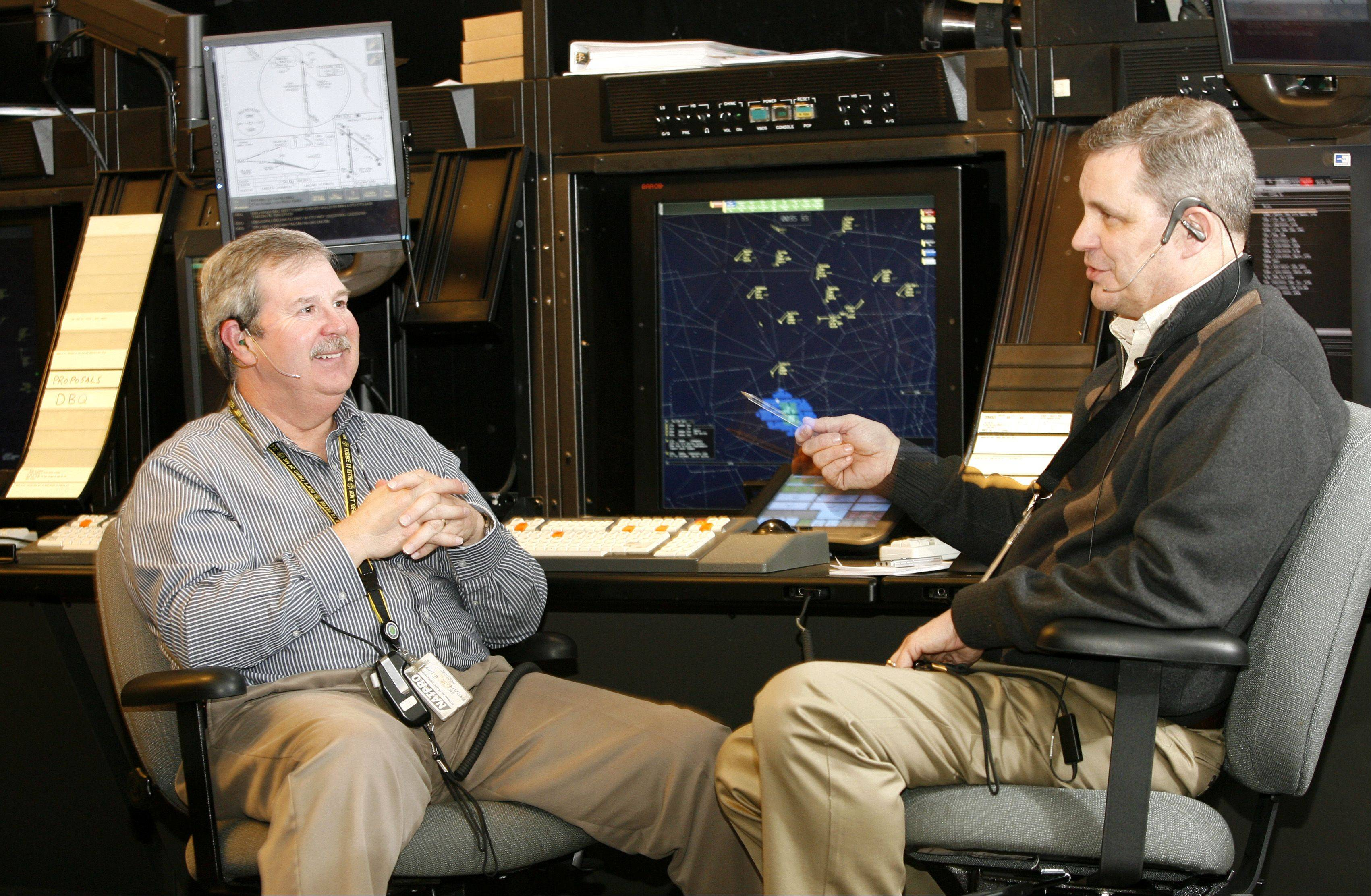 From their dynamic simulator area, traffic controllers Steve McGreevy, left and Guy Lieser, right, discuss how they maneuvered a distressed pilot back safely to the ground from the Air Route Traffic Control Center in Aurora. Their efforts earned them the prestigious Archie League Medal of Safety Award.