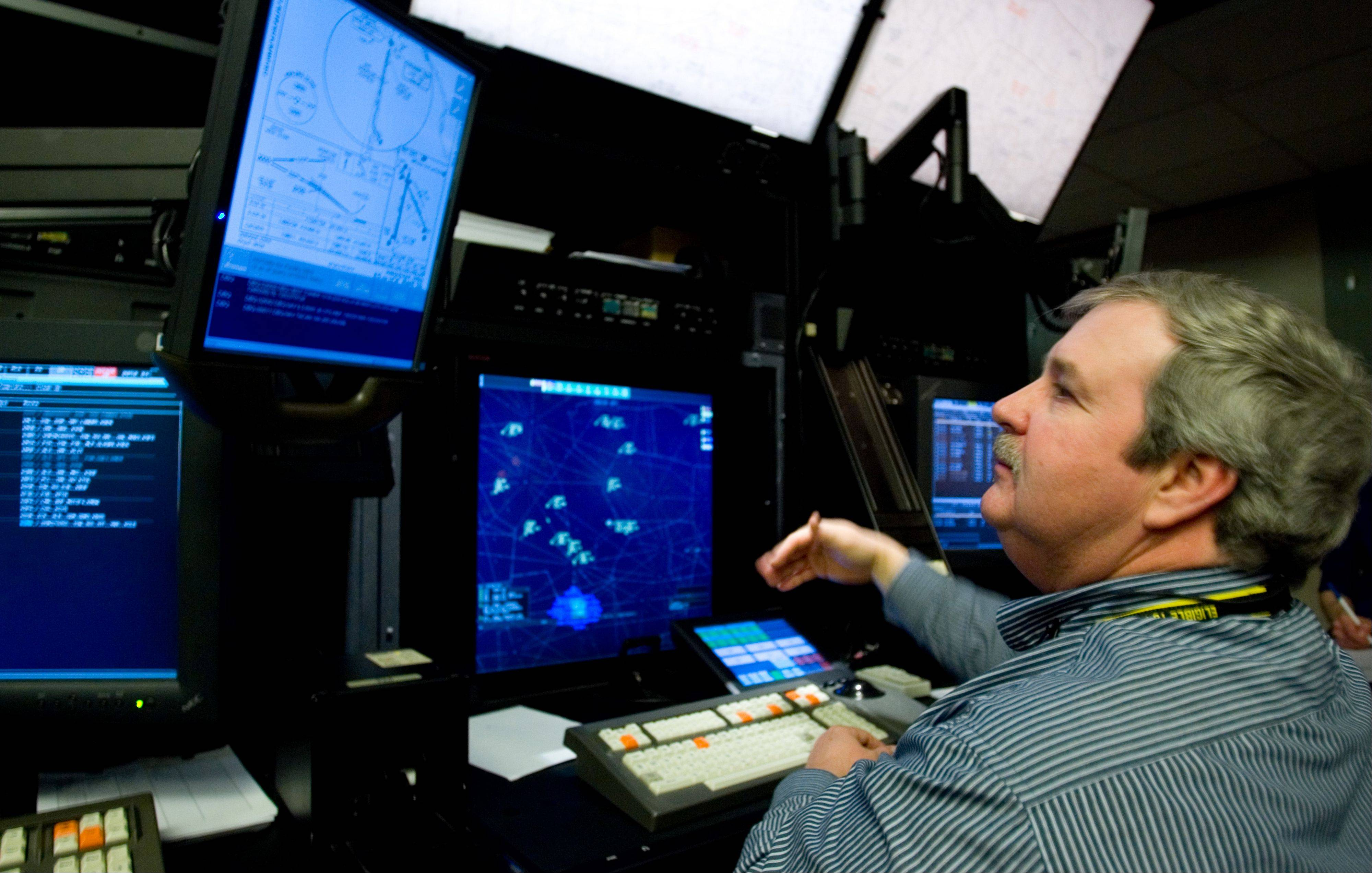 Traffic controller Steve McGreevy, above, discusses how he and his co-worker Guy Lieser maneuvered a distressed pilot back safely to the ground from the Air Route Traffic Control Center in Aurora. In their dynamic simulator is the approach plate for the specific airport that the pilot was guided to.