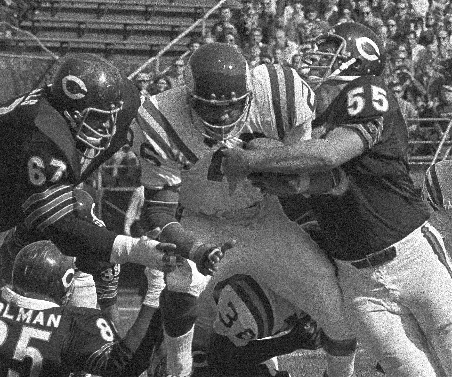 Clint Jones (26) of Minnesota gallops for five yards before being halted by George Seals (67) and Willie Holman (85), left and Doug Buffone (55), right, all of the Chicago Bears in first period, Sunday, Oct. 11, 1970, Chicago, Ill.