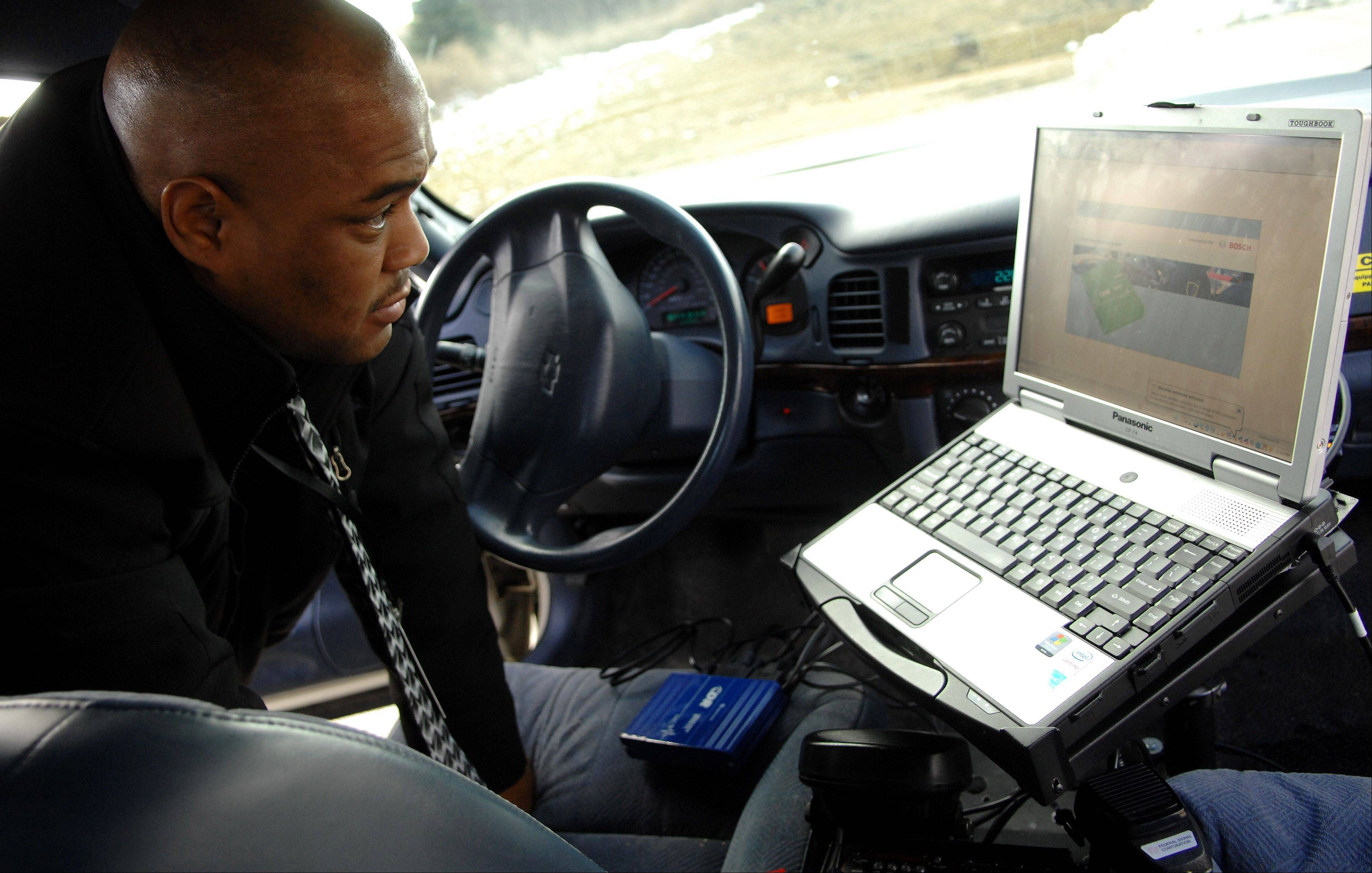 Craig Campbell of the Kane County sheriff's accident reconstruction team demonstrates how he runs a report using a crash data retrieval system that's hooked up to a squad car and a computer.