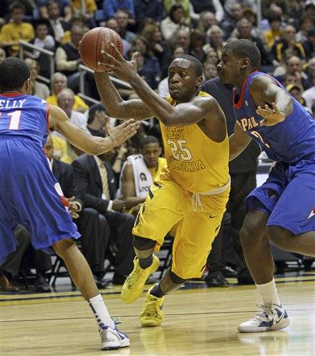 West Virginia's Darryl Bryant drives between DePaul's Jeremiah Kelly, left, and Edwind McGhee, right On Tuesday in WeSt Virgina. West Virginia won 92-75.