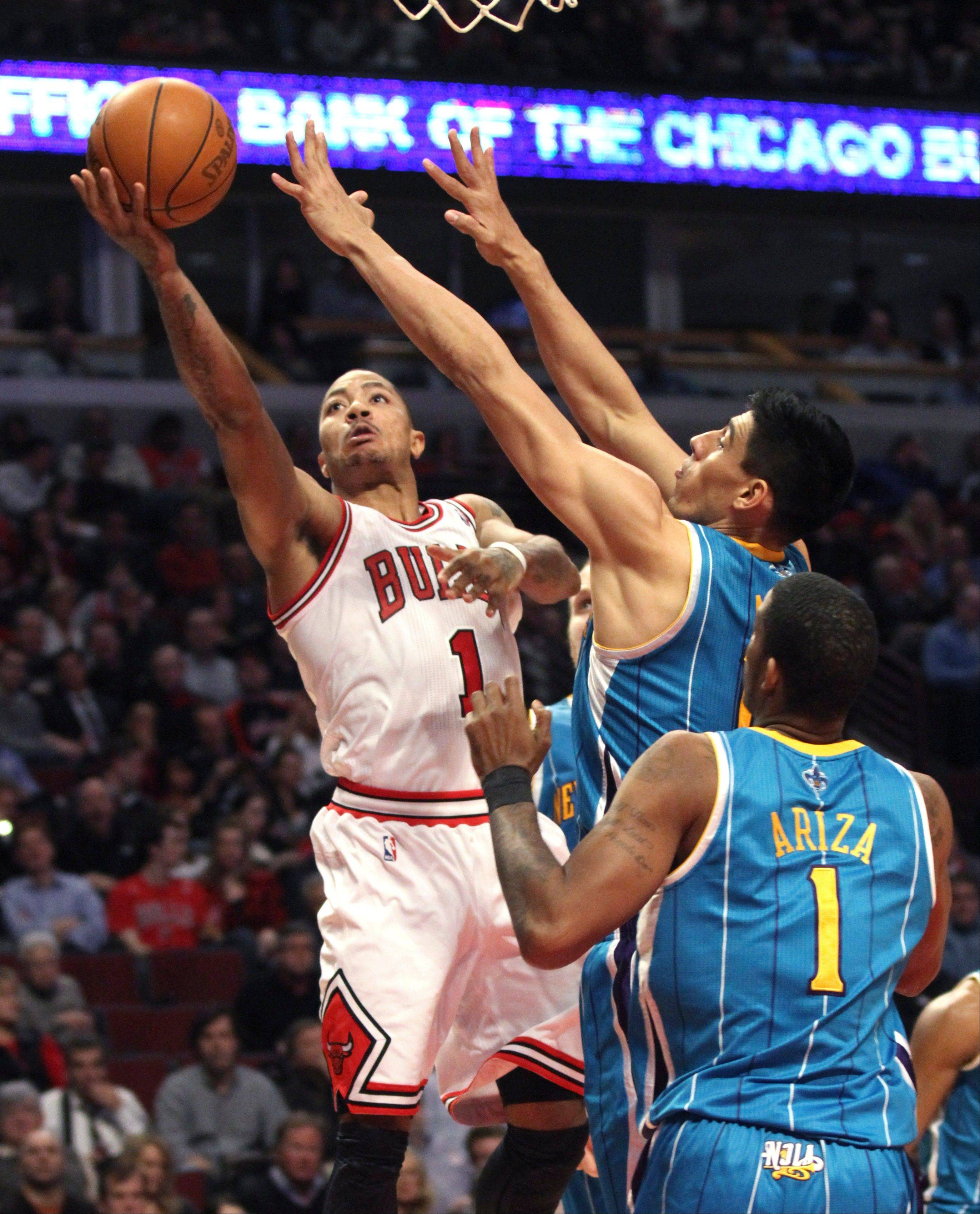 Derrick Rose shoots over the Hornets' Gustavo Ayon and Trevor Ariza on Tuesday night.