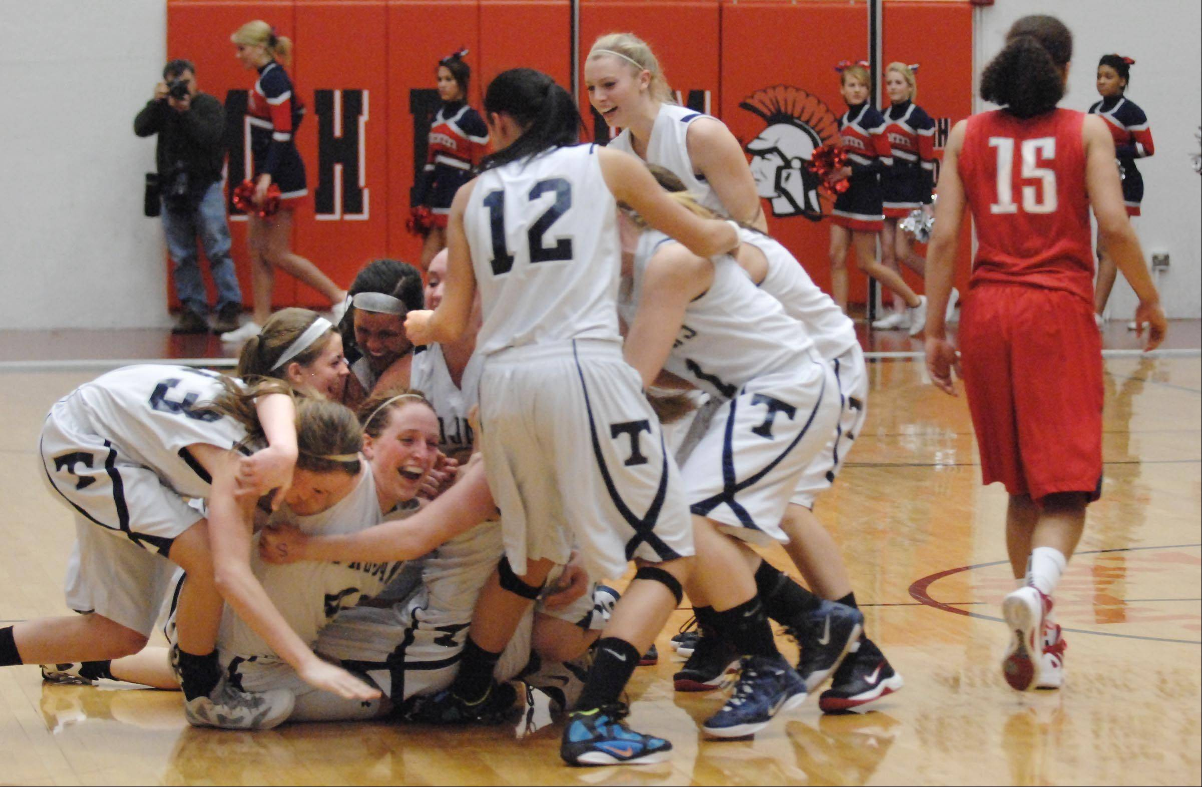 Cary-Grove celebrates their win as South Elgin's Becca Smith walks past at Tuesday's McHenry sectional basektball game.