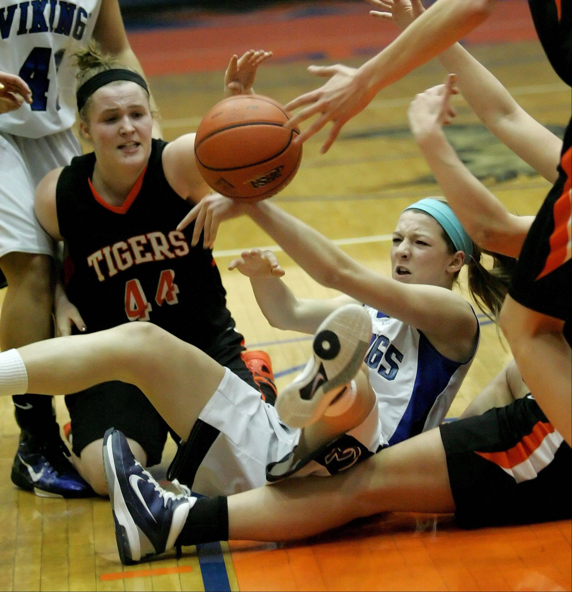 Olivia Linebarger of Wheaton Warrenville South, left and Michaela Loebel of Geneva tumble chasing a ball in Class 4A sectional semifinal girls basketball game at Hoffman Estates on Monday.