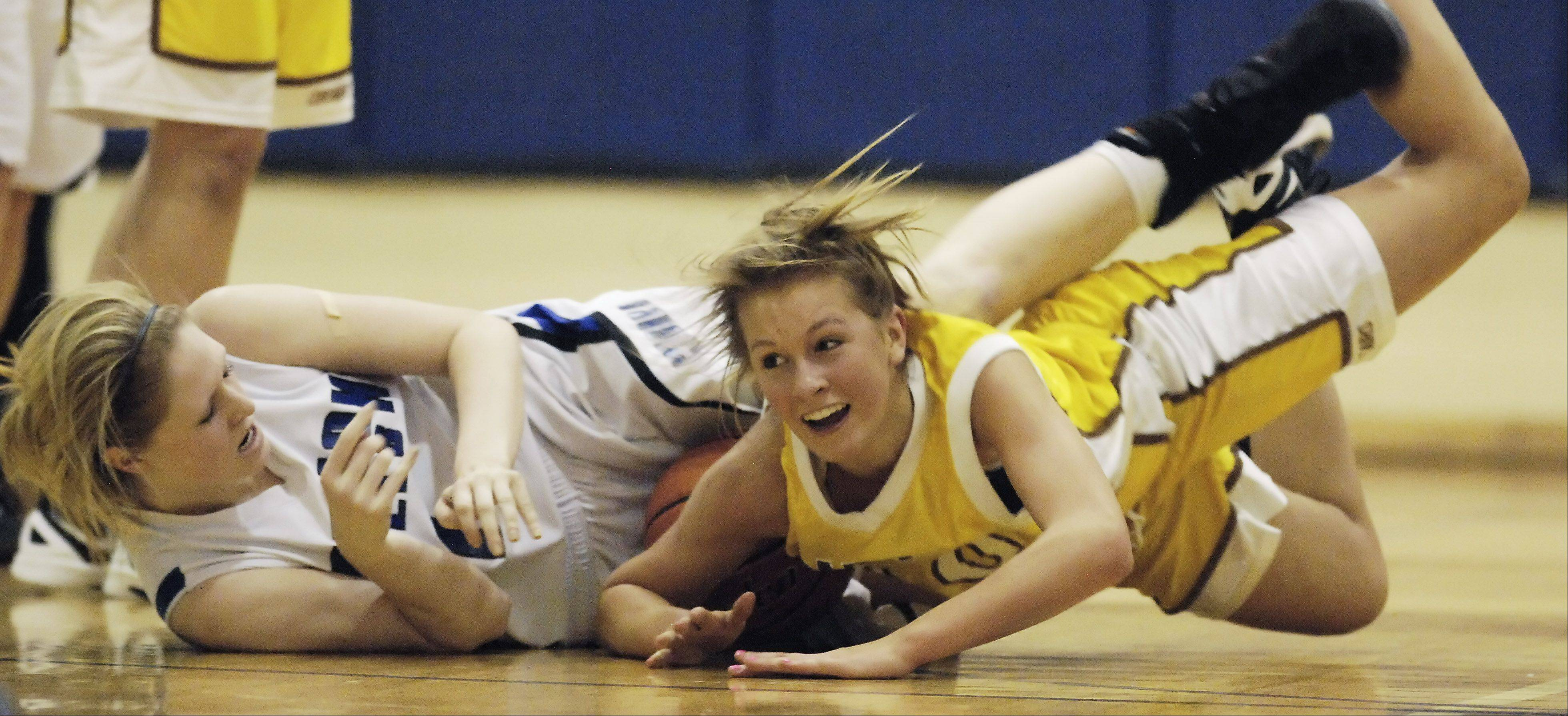 Vernon Hills' Sydney Smith, left, and Leah Lach of Carmel dive to the floor for a possession in Tuesday's game in Arlington Heights.