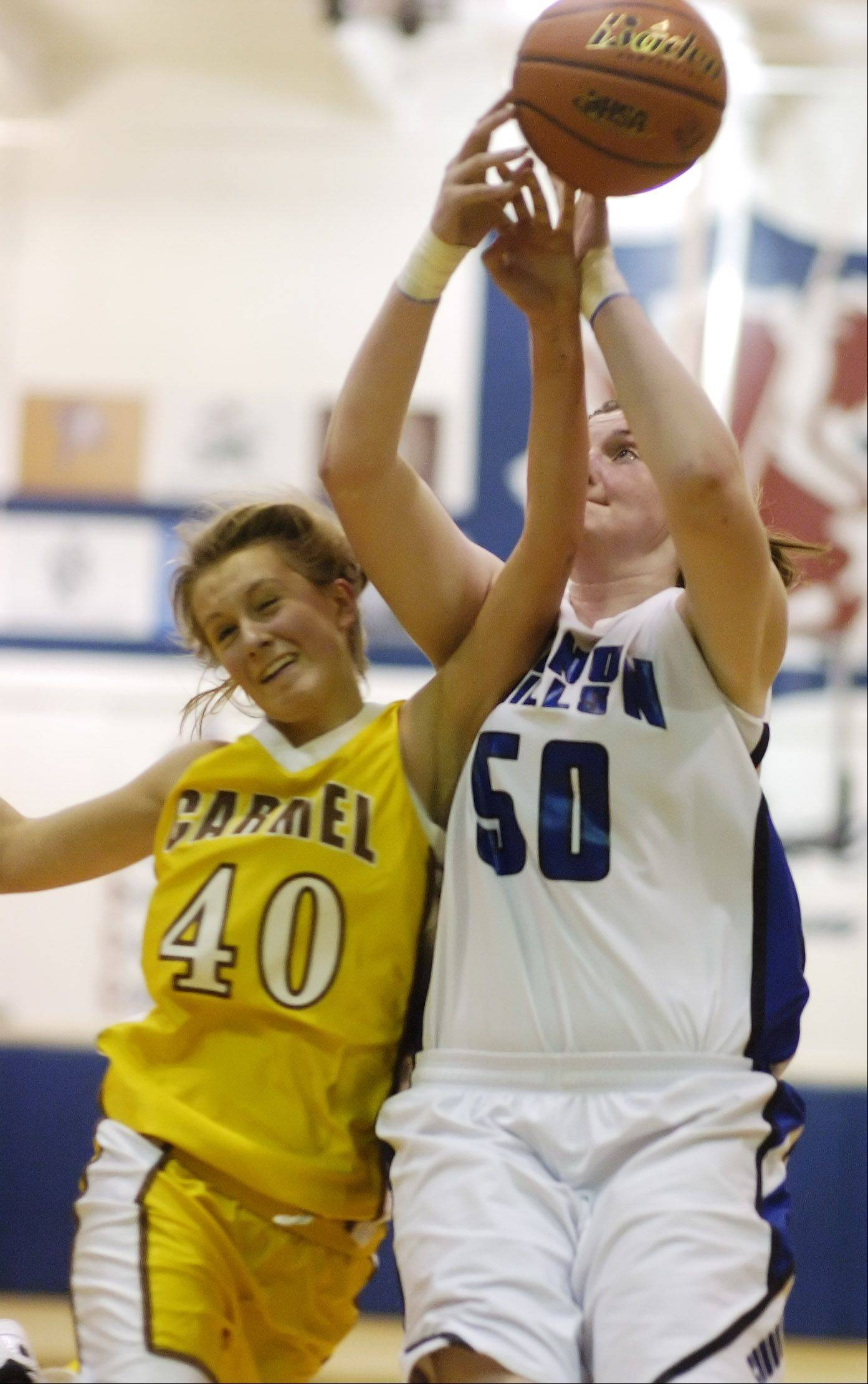 Carmel's Leah Lach, left and Vernon Hills' Meri Bennett-Swanson make contact during Tuesday's basketball game in Arlington Heights.
