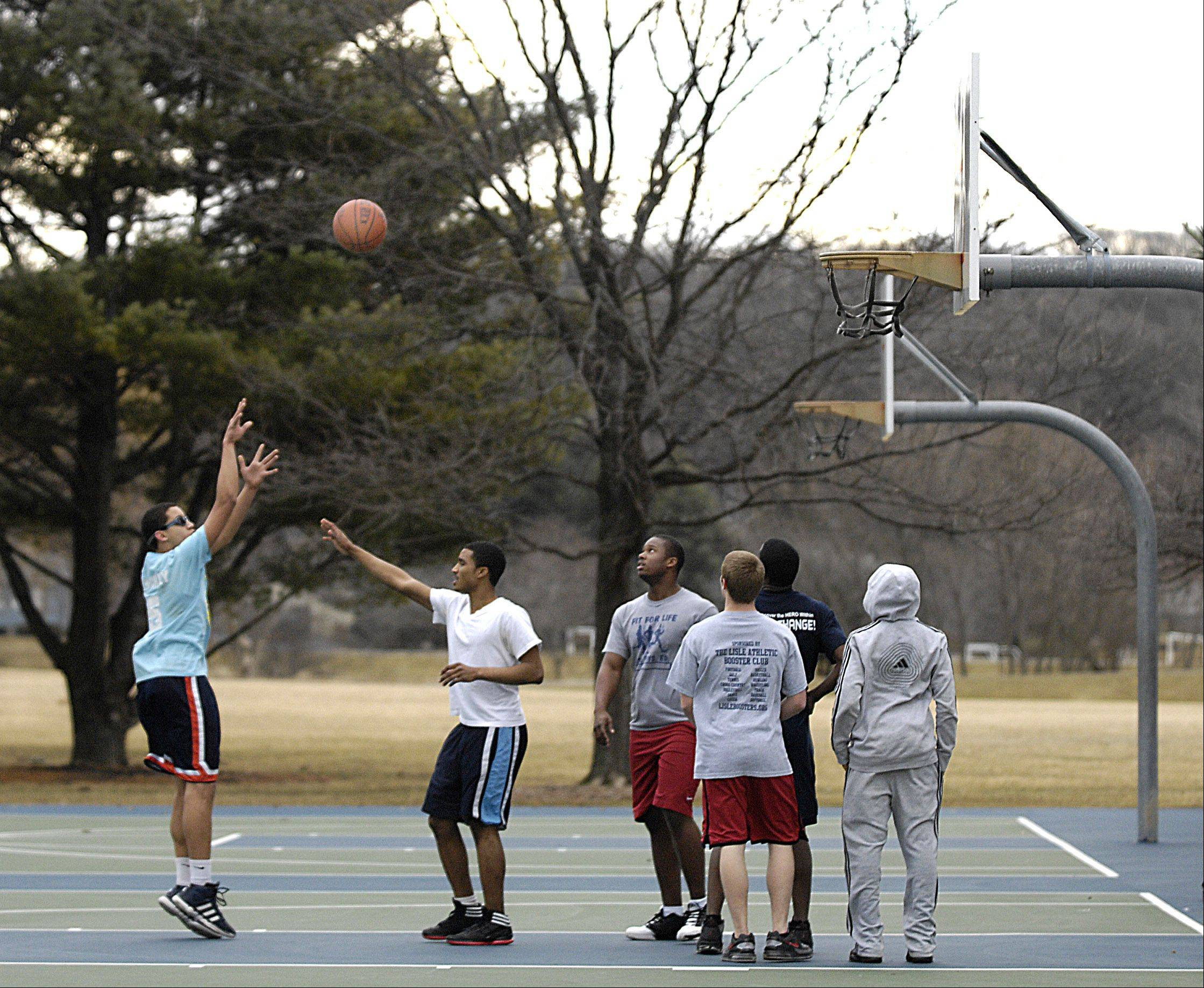 Teens play basketball at Community Park in Lisle. A warm winter has made it virtually a year-around sport this year.
