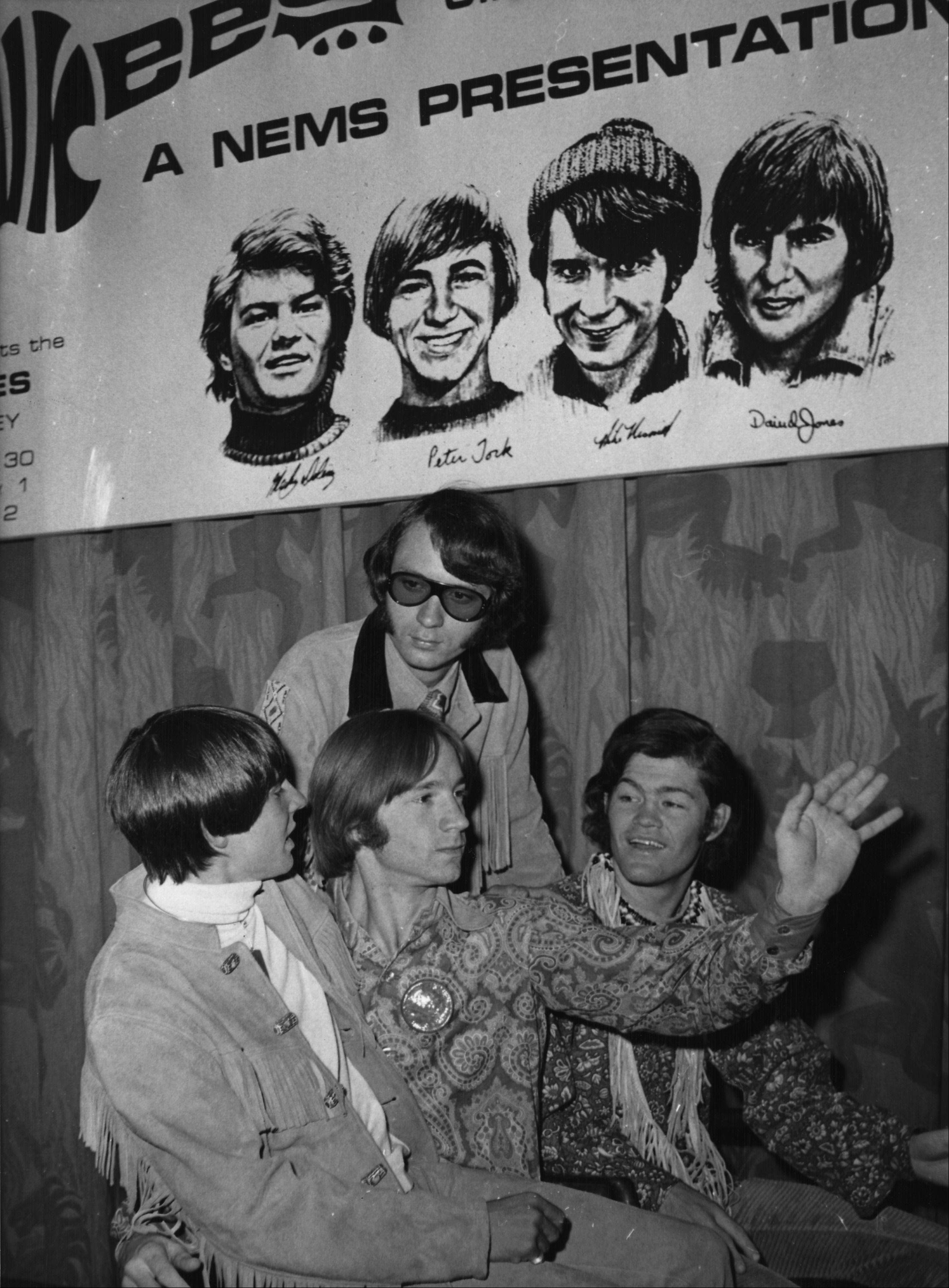 The U.S. American Pop band The Monkees, are seen beneath a poster with sketches of themselves, during their press conference in London, England, Thursday June 29, 1967. They are from left to right: Davy Jones, Peter Tork, Mike Nesmith and Mikey Dolenz.. The band arrived yesterday and will give their first concert tomorrow at the Empire Pool, here in London.