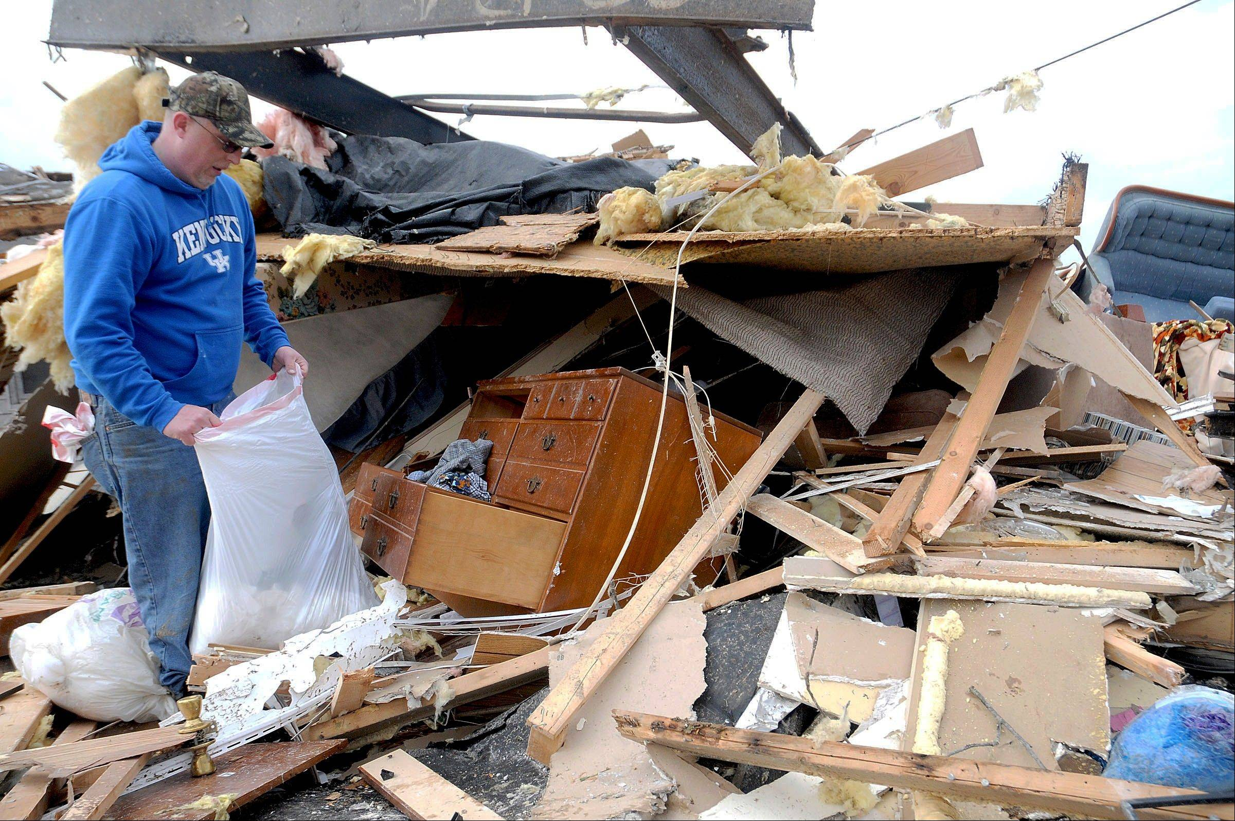 Roy Mauney of Harrisburg, Ill., collects clothes from a dresser in what remains of his parents house after a severe storm hit in the early morning hours on Wednesday, Feb. 29, 2012, in Saline County city. Mauney said his parents survived the storm by taking cover in a bathtub before their house blew off its foundation and across the street. A severe pre-dawn storm pounded portions of southern Illinois on Wednesday. Several deaths have been reported in Harrisburg and left the city's medical center scrambling to treat an influx of injured, the hospital's top administrator said.