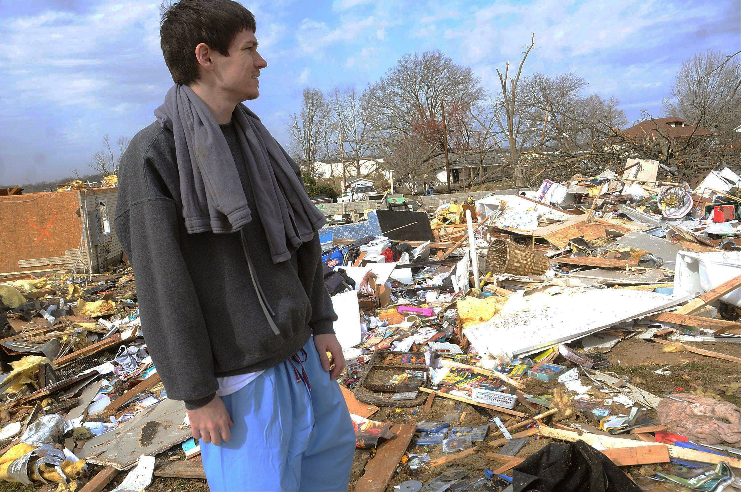 Shawn Anglin looks over the remains of his South Water Street home while retrieving belongings after a severe storm hit in the early morning hours on Wednesday, Feb. 29, 2012, in Harrisrbug, Ill. A severe pre-dawn storm pounded portions of southern Illinois on Wednesday. Several deaths have been reported in Harrisburg and left the city's medical center scrambling to treat an influx of injured, the hospital's top administrator said.