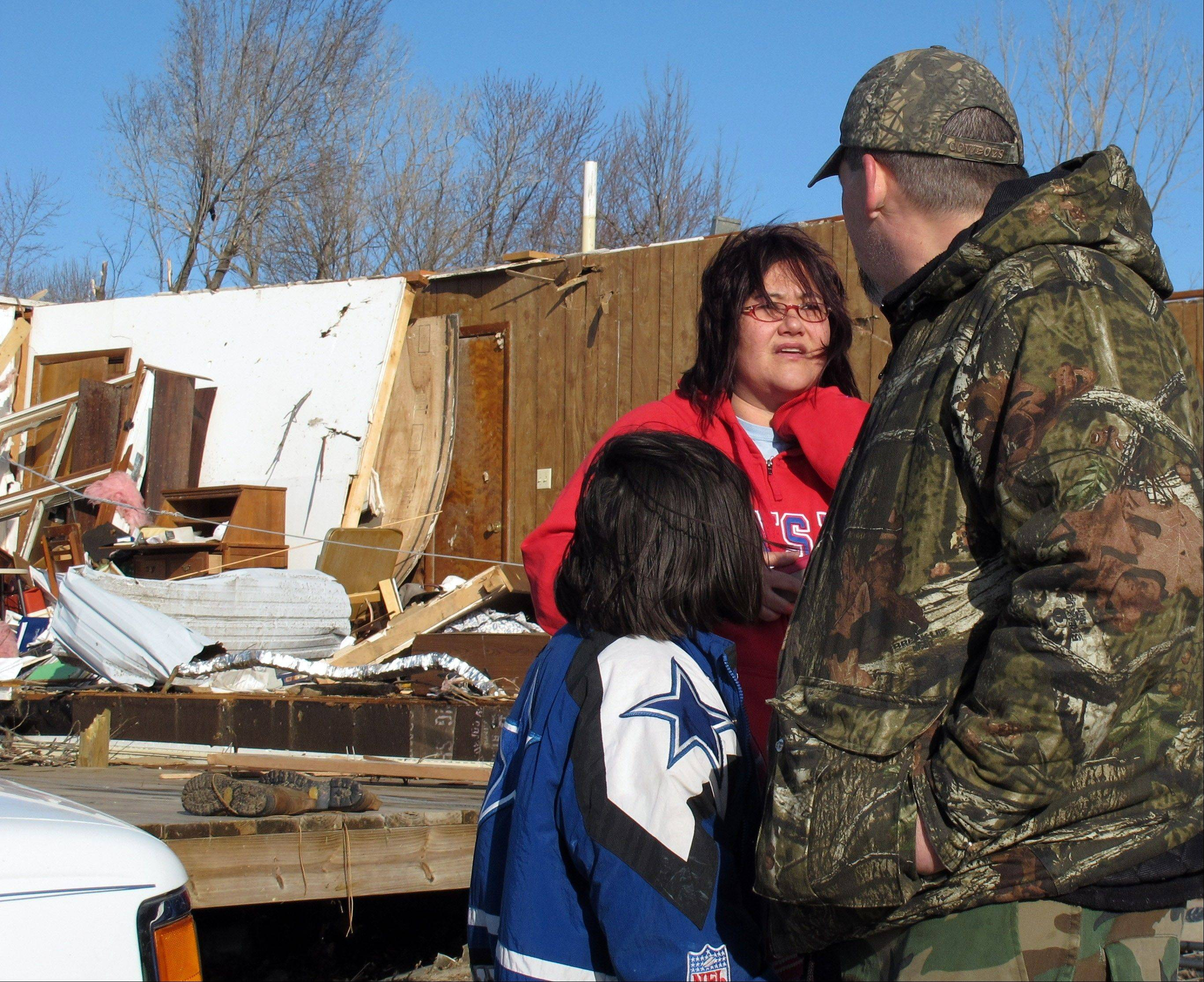 Tammy Woodyard, center, talks to neighbor Grant Hill, right, and his daughter, Talla, about the tornado damage to her father's home behind her, Wednesday, Feb. 29, 2012, in Harveyville, Kan.