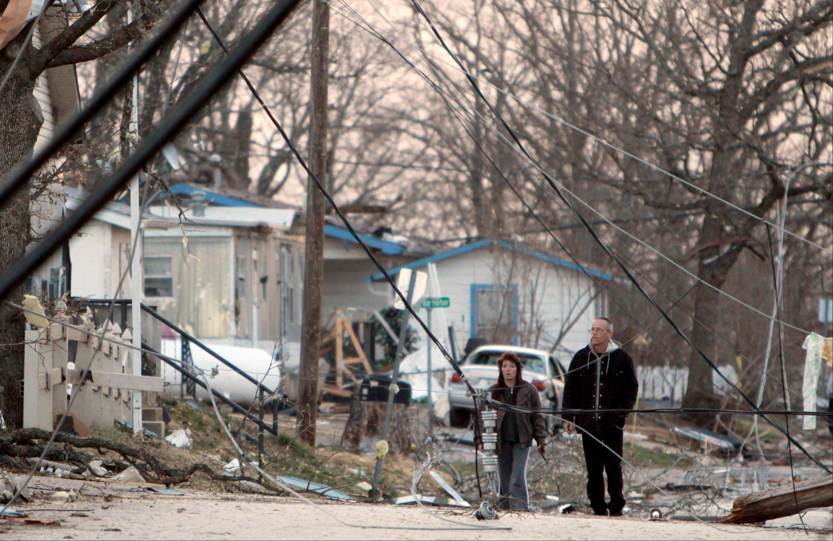 Residents walk amid downed power lines in their neighborhood in Branson, Mo, Wednesday, Feb. 29, 2012. A powerful storm system lashed the Midwest early Wednesday, roughing up the country music resort city of Branson and laying waste to a small town in Kansas.