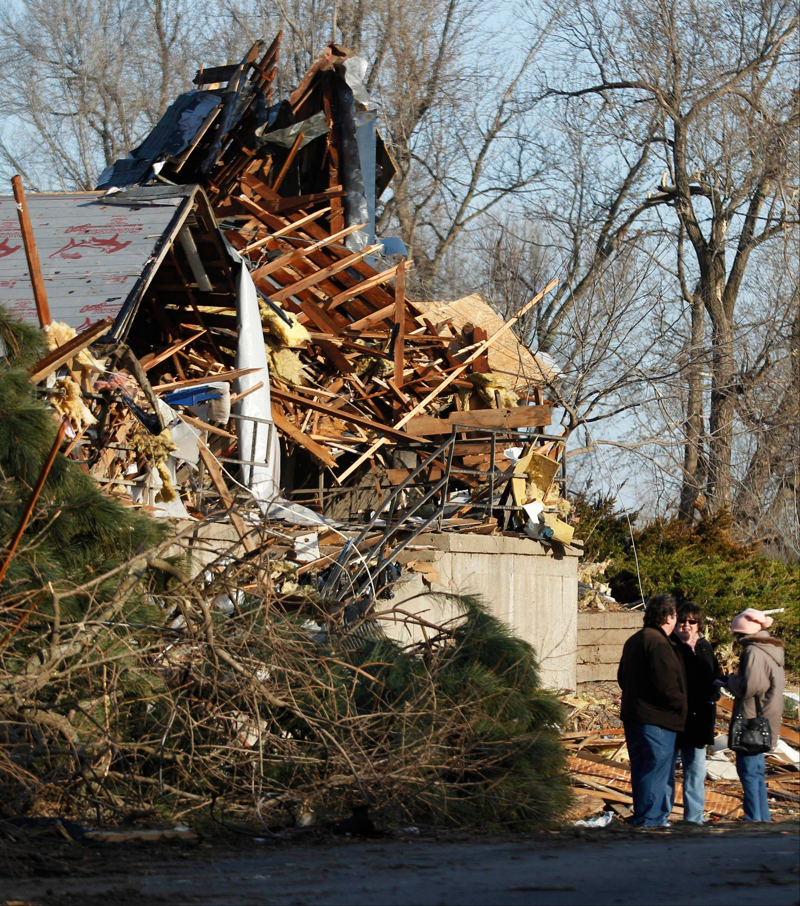 Residents talk in front of a home after severe storms destroyed several homes and businesses in Harveyville, Kan., Wednesday, Feb. 29, 2012.