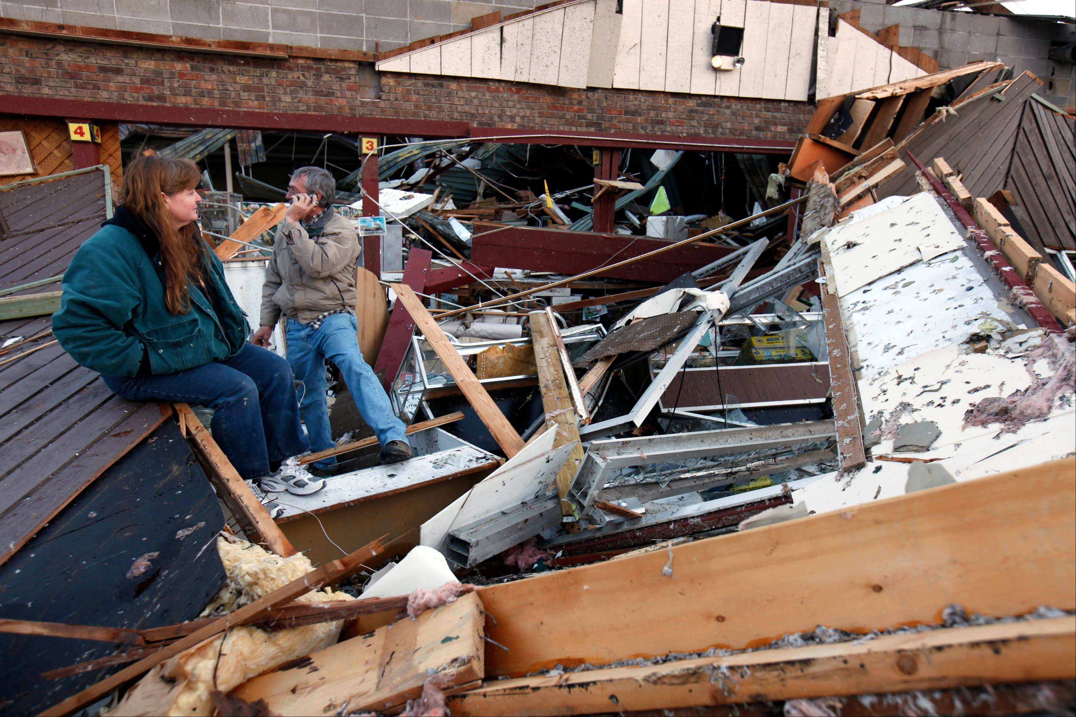 Sherry Cousins and her brother Bruce Wallace of Hollister, Mo., sit in the wreckage of their secondhand store in Branson, Mo, Wednesday, Feb. 29, 2012. A powerful storm system that produced multiple reports of tornadoes lashed the Midwest early Wednesday, roughing up the country music resort city of Branson.