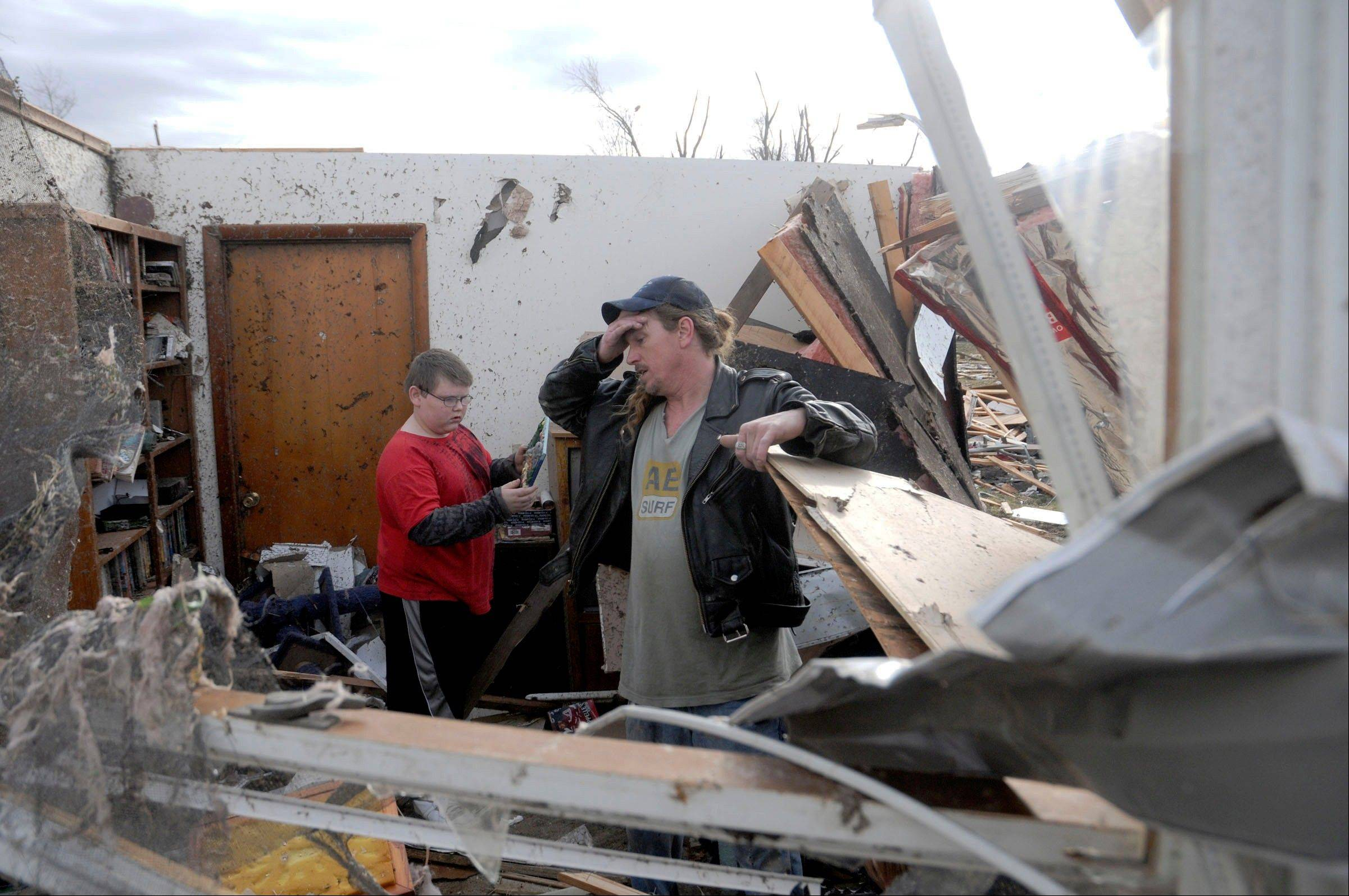 Gene Byrd pauses for a moment while he and his son Devyn Byrd, 14, look over some of the damage sustained to a friends house after a severe storm hit in the early morning hours on Wednesday, Feb. 29, 2012, in Harrisrbug, Ill. A severe pre-dawn storm pounded portions of southern Illinois on Wednesday. Several deaths have been reported in Harrisburg and left the city's medical center scrambling to treat an influx of injured, the hospital's top administrator said.